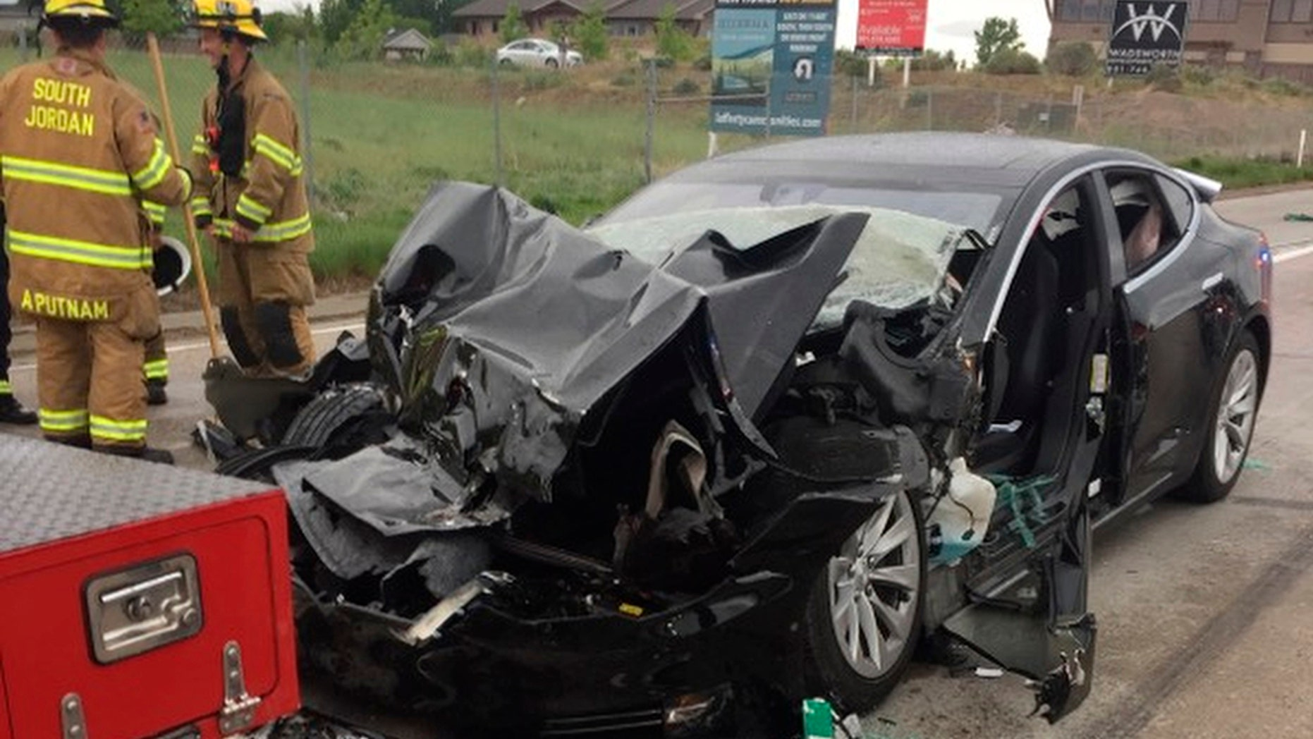 FILE -In this Friday, May 11, 2018, file photo released by the South Jordan Police Department shows a traffic collision involving a Tesla Model S sedan with a Fire Department mechanic truck stopped at a red light in South Jordan, Utah. The driver of a Tesla electric car that hit a Utah fire department vehicle over the weekend says the car's semi-autonomous Autopilot mode was engaged at the time of the crash. Police in the Salt Lake City suburb of South Jordan said Monday, May 14, 2018, the driver also said in an interview that she was looking at her phone before the accident. The 28-year-old woman broke her foot when her car hit a fire truck stopped at a red light while going 60 mph (97 kph). (South Jordan Police Department via AP, File)