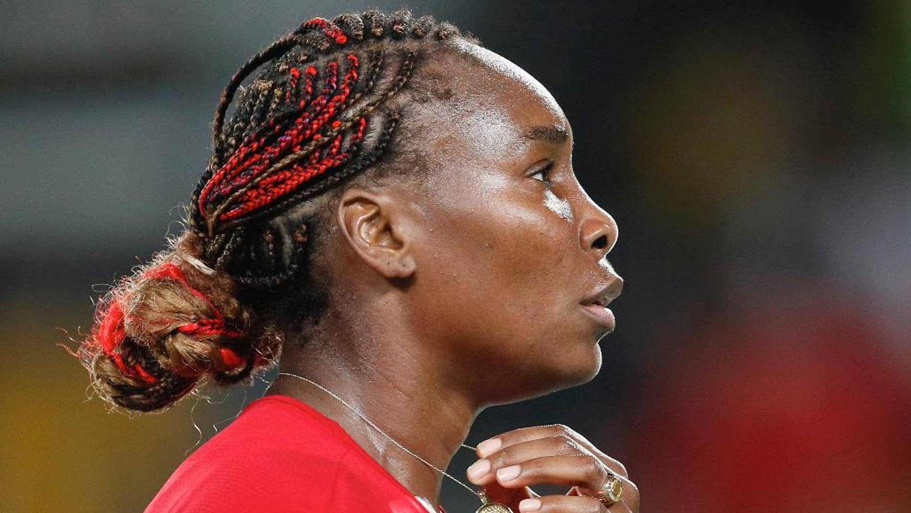 Venus Williams holds her medallion after losing a point to Belgium's Kirsten Flipkens in the women's tennis competition at the 2016 Summer Olympics in Rio de Janeiro, Brazil, Saturday, Aug. 6, 2016. (AP Photo/Vadim Ghirda)