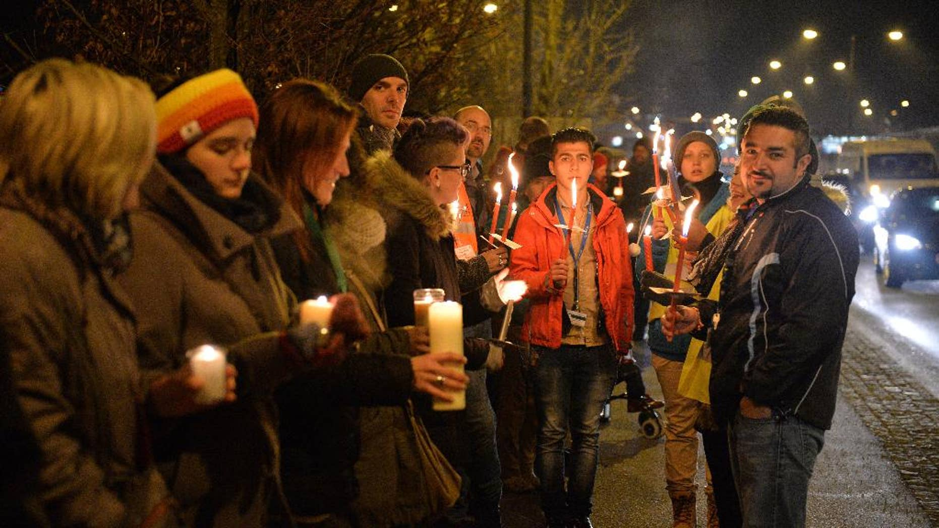 """Participants with candles and torches stand on a bridge at the border between Austria and Germany during a demonstration for """"Human refugee policy in a Europe without borders"""" in support of migrants, in Salzburg, Austria, Monday, Dec. 14, 2015. (AP Photo/Kerstin Joensson)"""