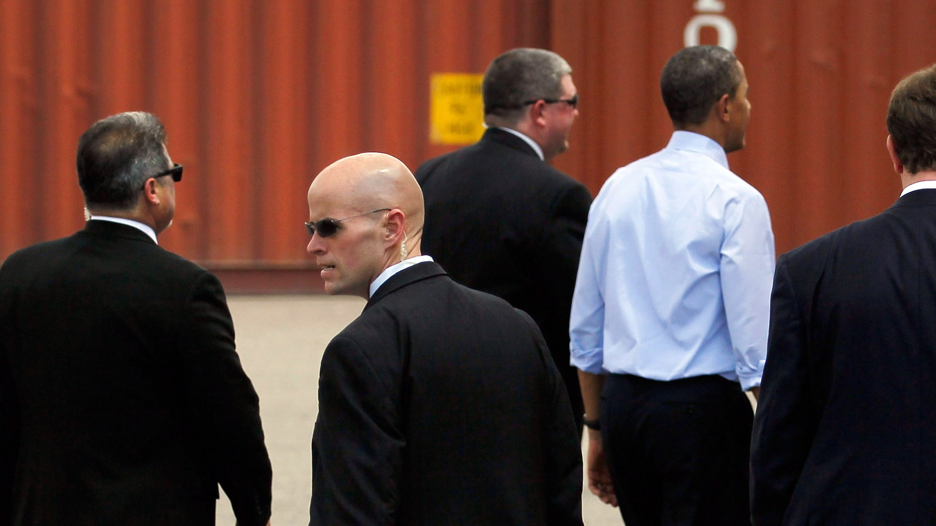 TAMPA, FL - APRIL 13:  U.S. President Barack Obama (blue shirt) surrounded by Secret Service agents walks away after a visit to the Port of Tampa on April 13, 2012 in Tampa, Florida. The President, on his way to the Summit of the Americas in Colombia, used the visit to emphasis small business trade with countries in Latin America.  (Photo by Joe Raedle/Getty Images)
