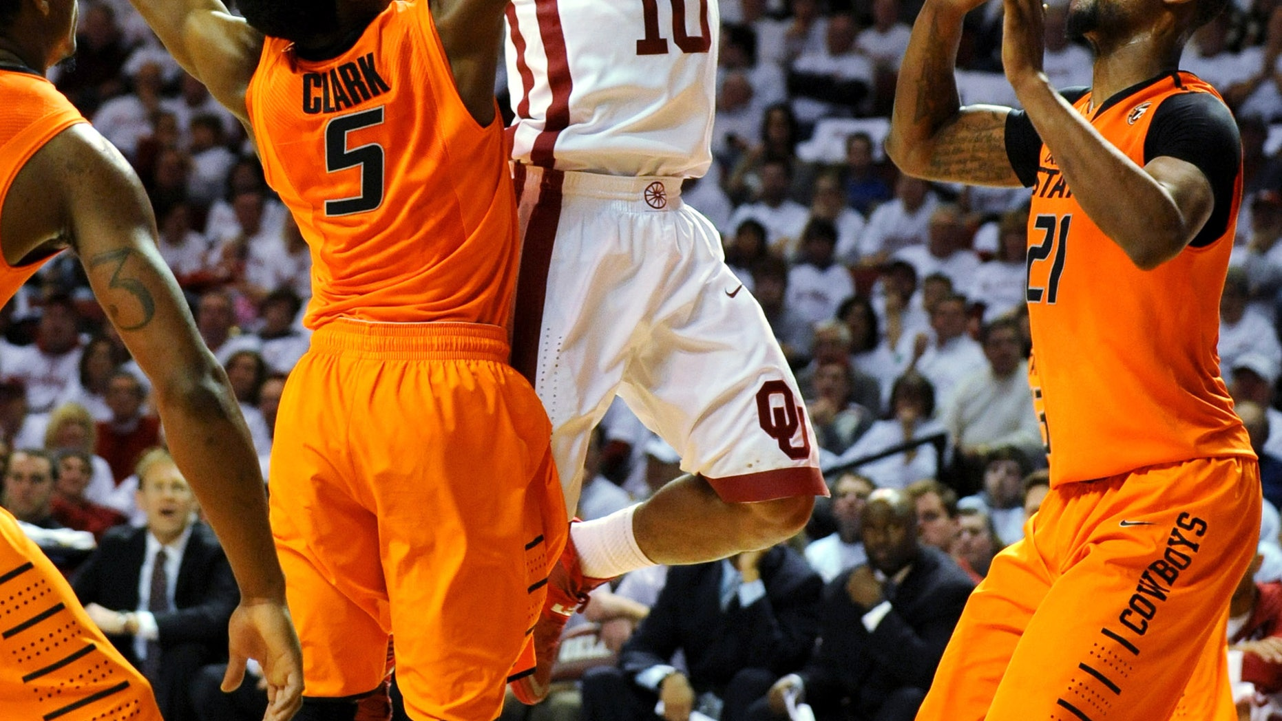 Oklahoma guard Jordan Woodard, center, takes a shot over Oklahoma State guard Stevie Clark, left, and Oklahoma State forward Kamari Murphy, right, during the second half of an NCAA college basketball game in Norman, Okla., Monday, Jan. 27, 2014. Woodard scored 18 points in the 88-76 win over rival Oklahoma State. (AP Photo/Brody Schmidt)