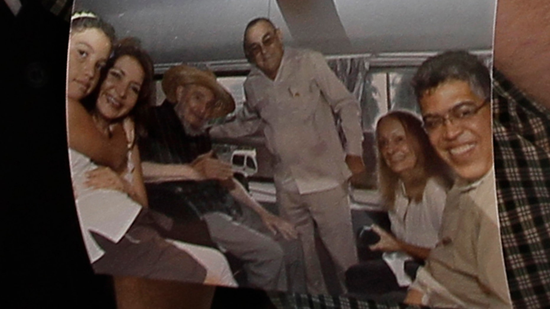Former Venezuelan Vice President Elias Jaua shows a picture of Cuba's leader Fidel Castro,  third from left,  at the Hotel Nacional in Havana Sunday Oct. 21, 2012. According to Jaua, the picture was taken Saturday Oct. 20, 2012  inside a van outside the hotel. (AP Photo/Franklin Reyes)