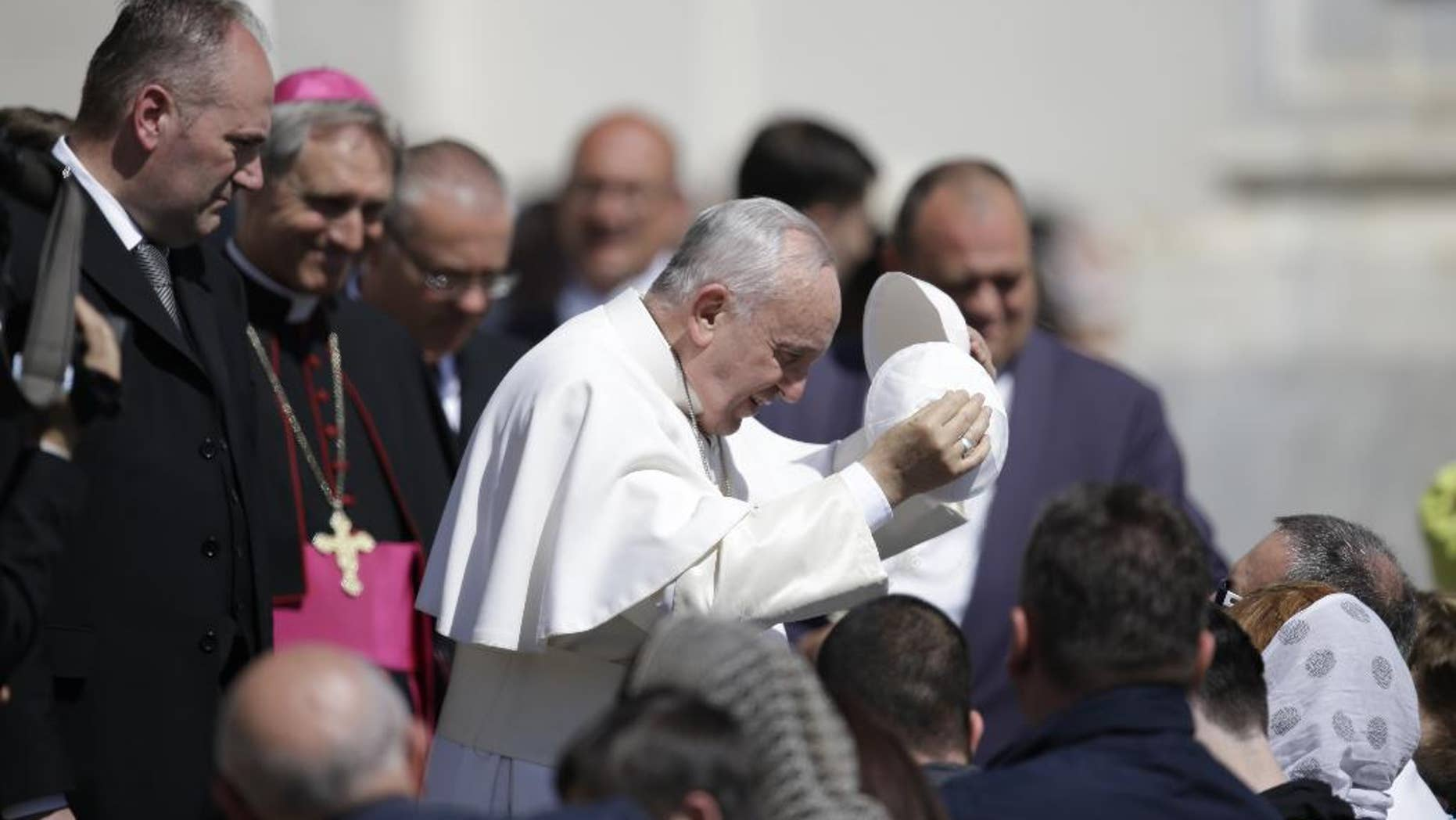 Pope Francis, center, exchanges his skull cap with one donated to him by a pilgrim as he leaves at the end of his weekly general audience, in St. Peter's Square, at the Vatican, Wednesday, April 22, 2015. (AP Photo/Gregorio Borgia)