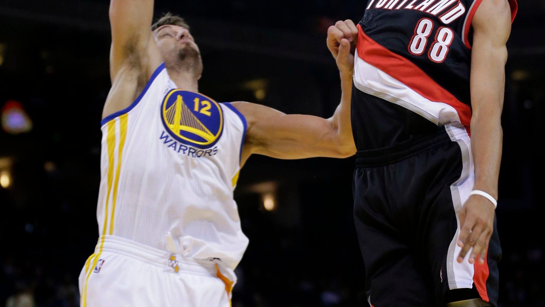 Portland Trail Blazers' Nicolas Batum (88) shoots over Golden State Warriors' Andrew Bogut during the first half of an NBA preseason basketball game on Thursday, Oct. 24, 2013, in Oakland, Calif. (AP Photo/Marcio Jose Sanchez)