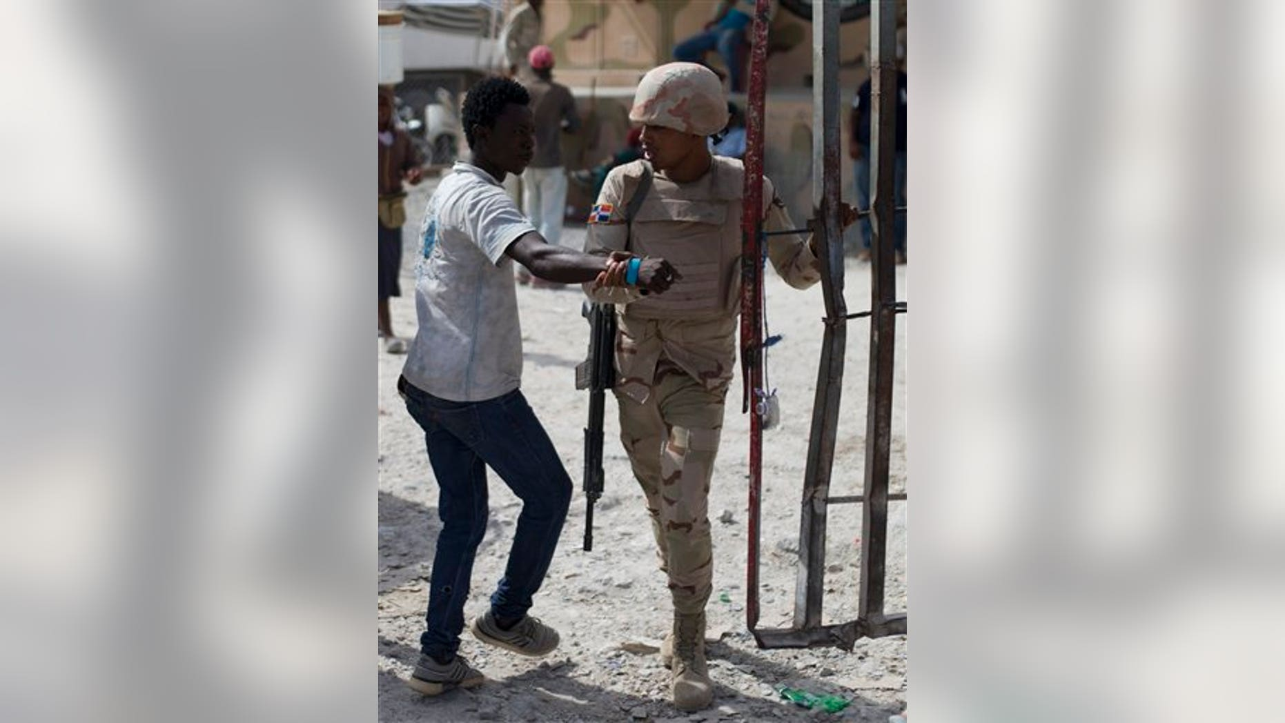 A Haitian man who tried to slip through is pulled back toward the Haitian side of the border by a Dominican soldier, in Malpasse, Haiti, Wednesday, June 17, 2015.