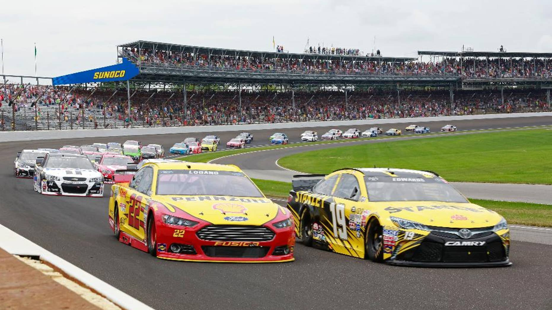 July 26, 2015: Carl Edwards (19) and Joey Logano (22) lead the field through the first turn on the start of the NASCAR Brickyard 400 auto race at Indianapolis Motor Speedway in Indianapolis.