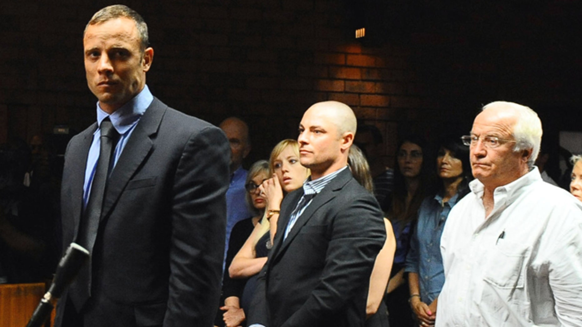 Feb. 19, 2013: Olympian Oscar Pistorius stands following his bail hearing, as his brother Carl, center, and father Henke look on, in Pretoria, South Africa.