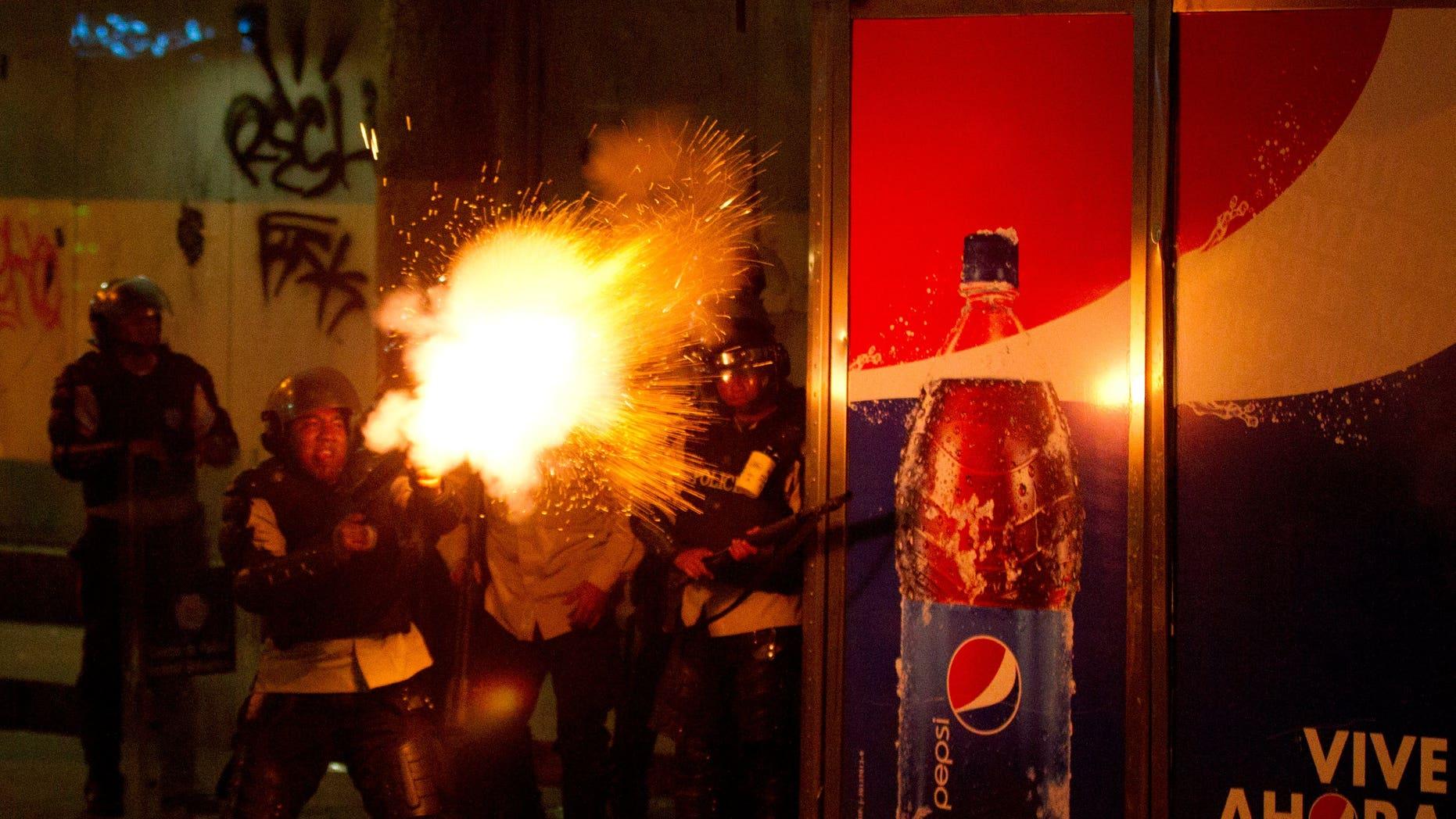 Un policía nacional bolivariano dispara gases lacrimógenos contra manifestantes antigubernamentales en Caracas, Venezuela, el sábado 22 de marzo de 2014. (Foto AP/Esteban Félix)