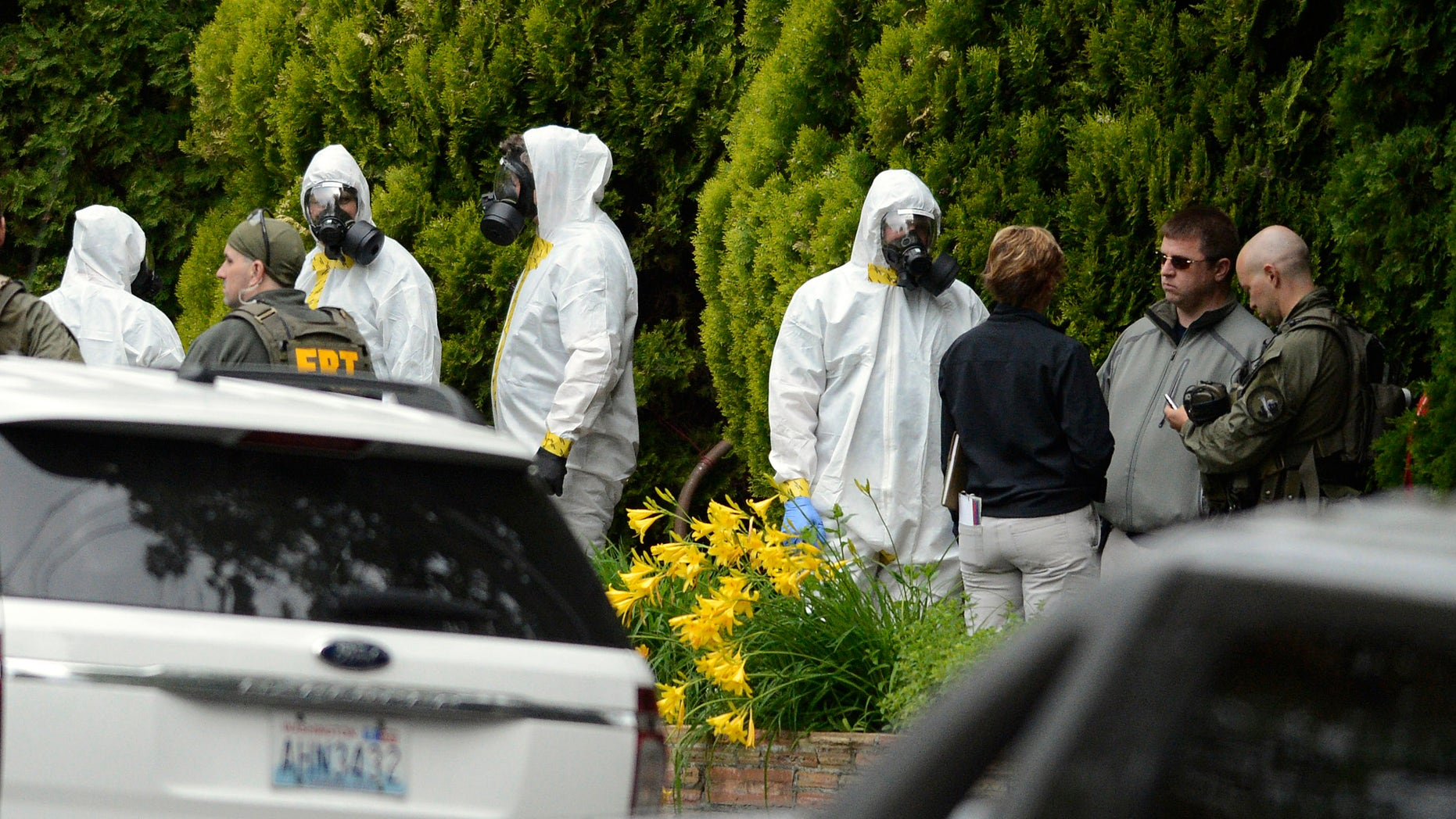 During the execution of a search warrant, members of the Joint Federal Haz-Mat Team, FBI, and local law enforcement gather in front of the Osmun Apartments near the intersection of First Avenue and Oak Street in Browne's Addition on Saturday, May 18, 2013 in Spokane, Wash. The search warrant is in connection with ricin-laced letters intercepted at a Post Office facility in Spokane earlier in the week. (AP Photo/TheSpokesman-Review, Colin Mulvany) COEUR D'ALENE PRESS OUT