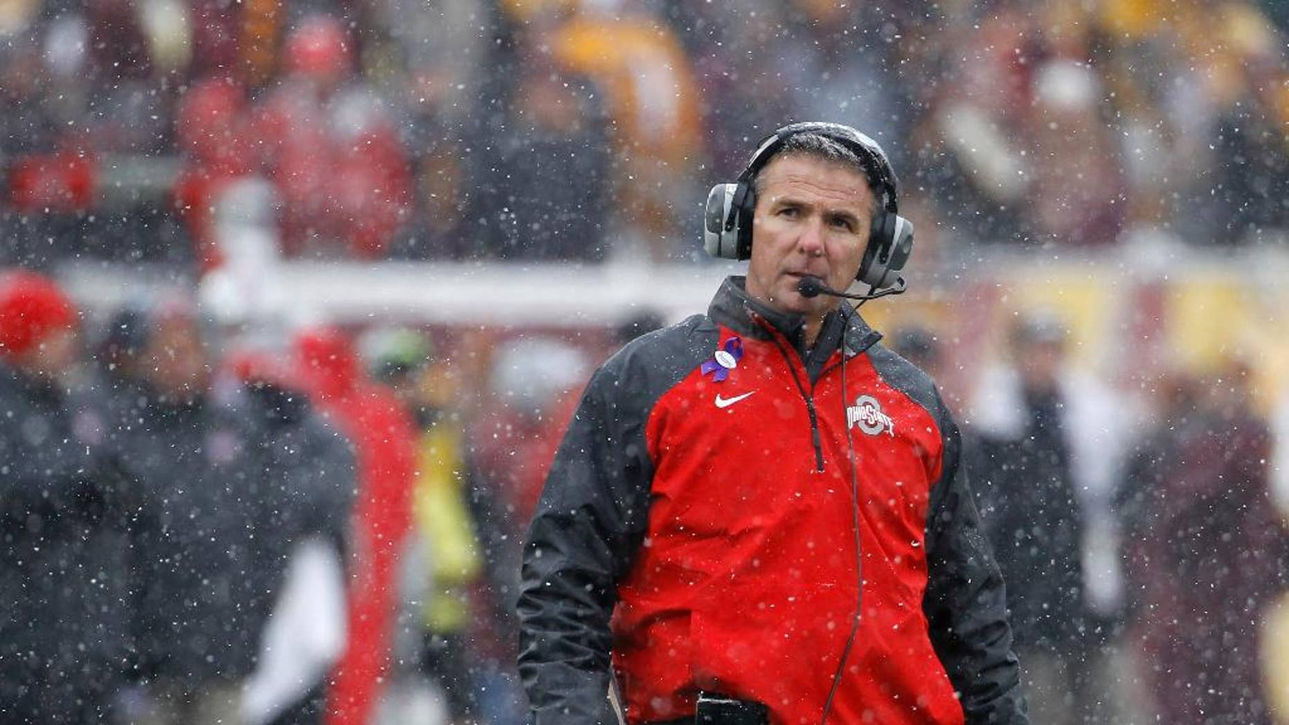 Ohio State head coach Urban Meyer walks out to his players in a timeout as snow falls during the fourth quarter of an NCAA college football game against Minnesota in Minneapolis Saturday, Nov. 15, 2014. Ohio State won 31-24. (AP Photo/Ann Heisenfelt)