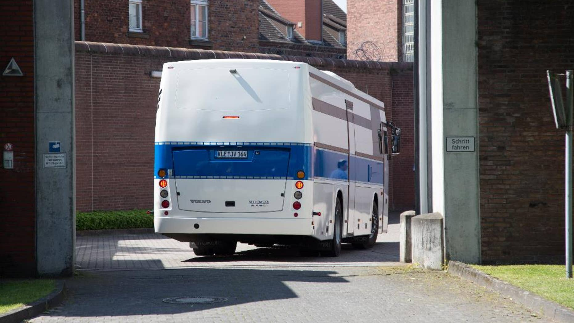 A bus for prisoners drives into the prison in Muenster, western Germany, Thursday, July 7, 2016. More than 500 inmates are being evacuated from the prison after experts said parts of the building were so dilapidated they could collapse any time. (Friso Gentsch/dpa via AP)