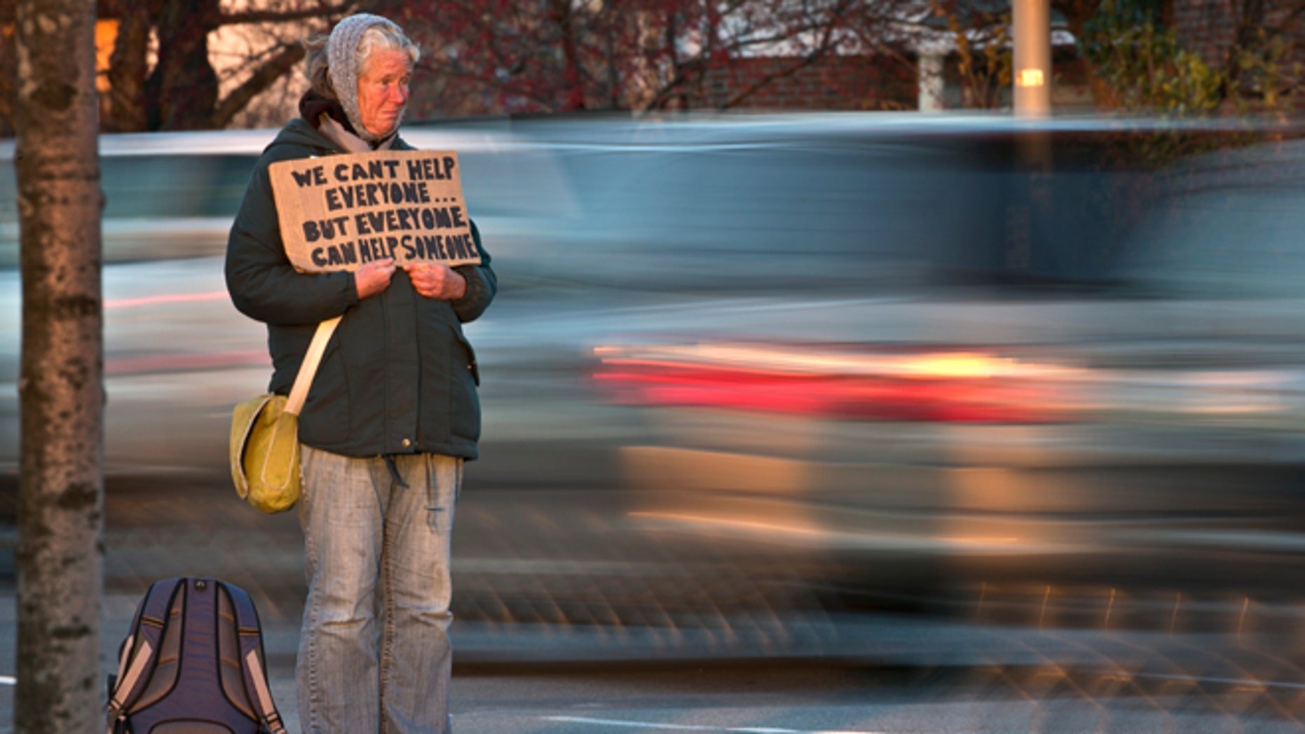 FILE - Nov. 14, 2013: Susan St. Amour, 54, a homeless woman, panhandles during the evening commute in Portland, Maine.