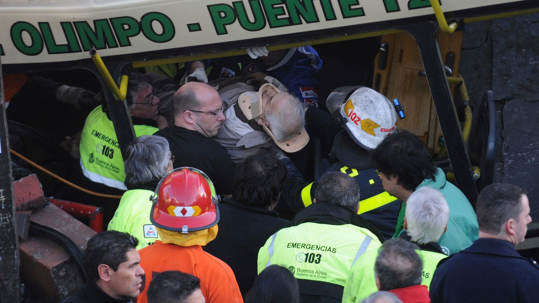 A wounded passenger is carried out a train after it crashed in Buenos Aires, Argentina, Tuesday, Sept. 13, 2011. At least seven people were killed and at least 162 injured in a rush-hour crash Tuesday involving two passenger trains and a bus whose driver drove around barriers in an attempt to beat them across the tracks, Argentine authorities said.