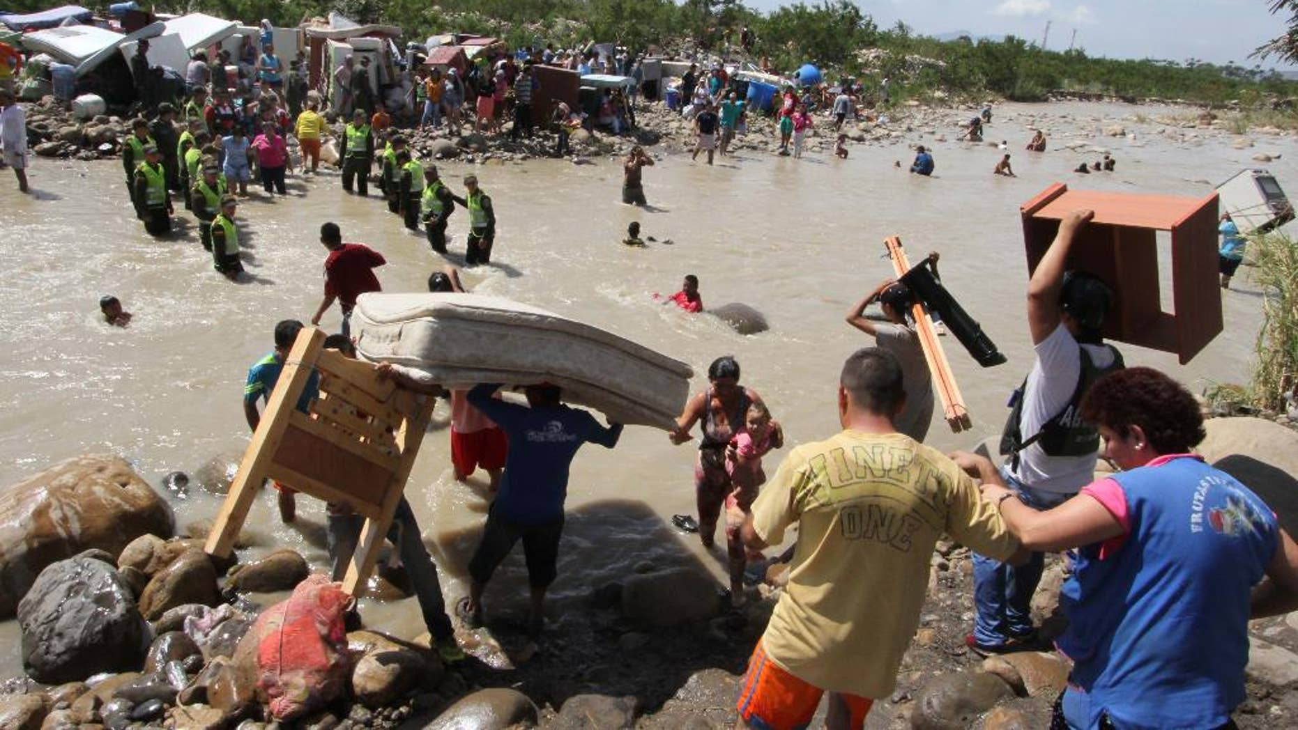 In this Tuesday, Aug. 25, 2015 photo, people carry their household belongings across the Tachira River from Venezuela, foreground, to Colombia, near San Antonio del Tachira, Venezuela, during a mass exodus of Colombians living on the Venezuelan side of the border. Venezuelan President Nicolas Maduro vowed to extend a crackdown on illegal migrants from neighboring Colombia he blames for rampant crime and widespread shortages, while authorities across the border struggled to attend to droves of returning deportees.  (AP Photo/Eliecer Mantilla)
