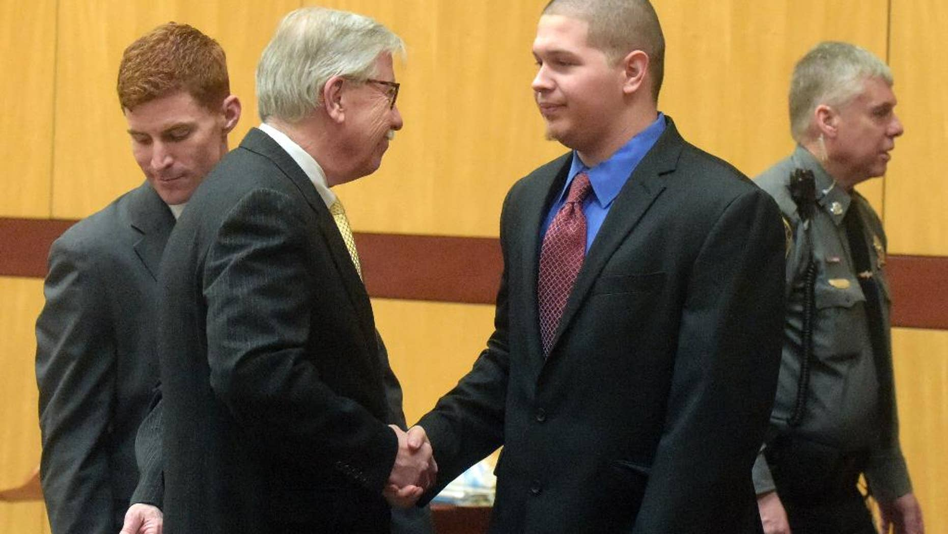 Defendant Tony Moreno, center right, shakes hands with Frederick O'Brien, one of his defense attorneys, after walking into a courtroom at Middletown Superior Court, Friday, Feb. 10, 2017, in Middletown, Conn. Moreno is charged with killing his 7-month-old son by throwing the boy off a bridge. (Patrick Raycraft/Hartford Courant via AP, Pool)