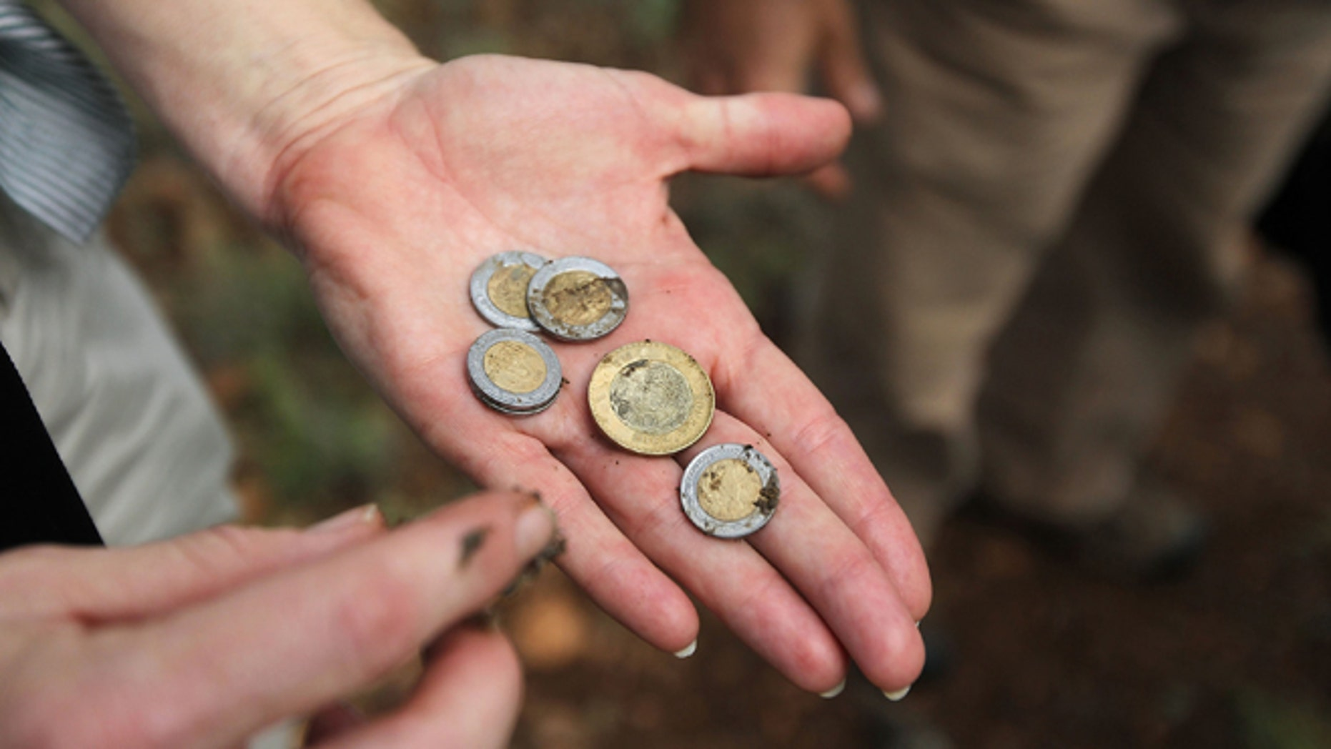 GREEN VALLEY, AZ - JULY 31:  Volunteer Rebecca Fowler displays Mexican pesos found in a backpack discarded by immigrants crossing into Arizona from Mexico along a backcountry trail on July 31, 2010 near Green Valley, Arizona. She was on a patrol for the non-profit group Samaritans, which delivers water to points near the U.S. Mexico border for immigrants crossing illegally into Arizona. Samaritans volunteers also provide medical assistance for distressed migrants, who often suffer from severe dehydration while crossing the desert. Immigrant aid groups and law enforcement alike say that the number of immigrants crossing illegally into Arizona from Mexico has slowed dramatically in 2010, with jobs scarce due to the U.S. recession and widespread fear in the Latino community associated with Arizona's new immigration enforcement law SB 1070. (Photo by John Moore/Getty Images) *** Local Caption *** Rebecca Fowler