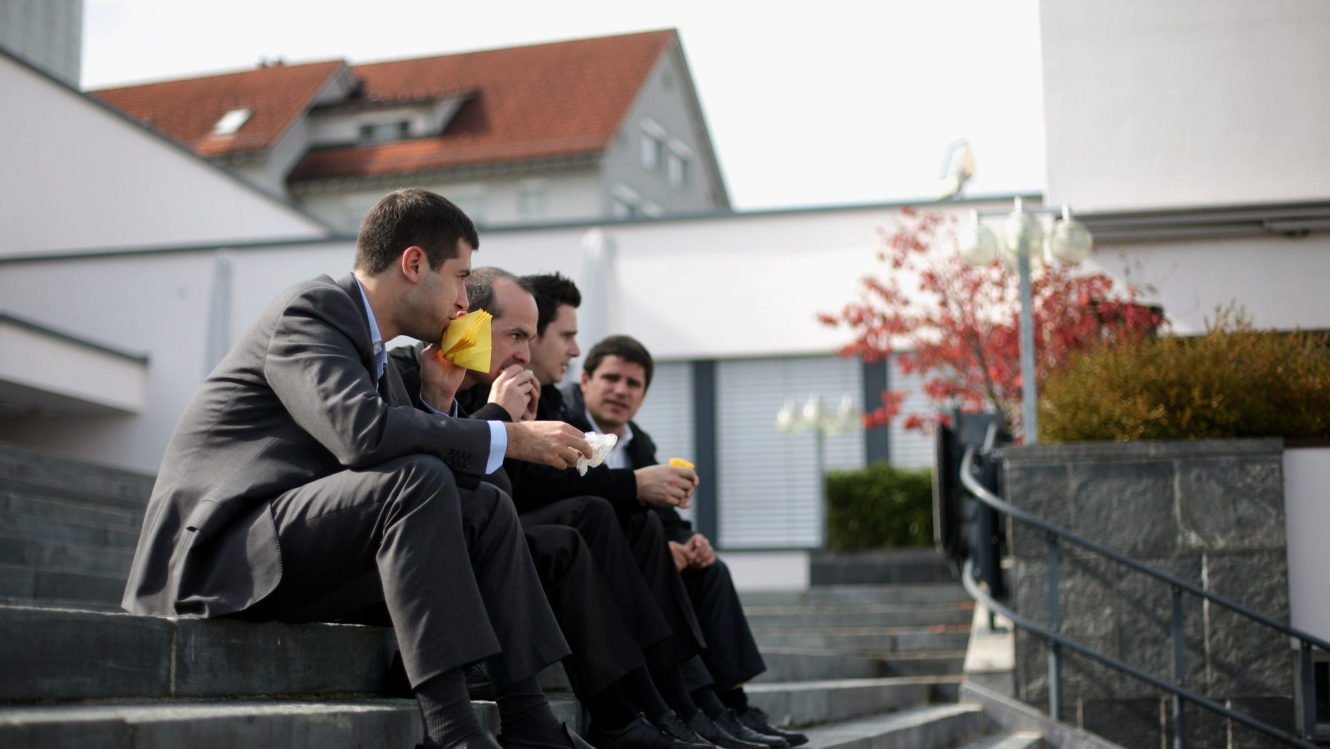 PFAEFFIKON, SWITZERLAND - OCTOBER 06: Four men eat sandwiches during lunch time as they sit on the steps of the village square on October 6, 2009 in Pfaeffikon, Switzerland. Due to lower taxes and less regulation the small Swiss town on the shores of lake Zurich has become a hedge fund hot spot.  (Photo by Miguel Villagran/Getty Images)