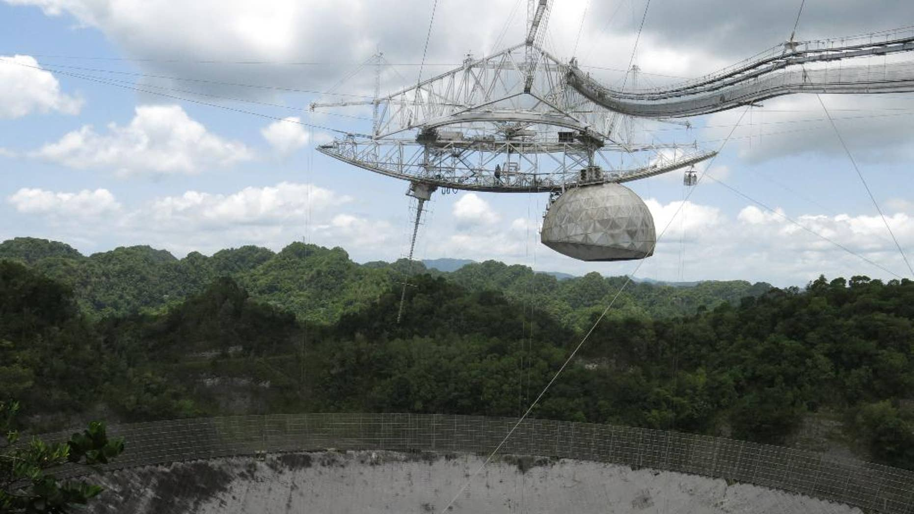 This July 13, 2016 photo shows the world's largest single-dish radio telescope at the Arecibo Observatory in Arecibo, Puerto Rico. Dwindling funds from the U.S. government and construction of bigger, more powerful telescopes in places like China and Chile are threatening this telescope's existence. It performs tasks like searching for gravitational waves, listening for extraterrestrial signals and tracking asteroids that might be on a collision course with Earth.  (AP Photo/Danica Coto)