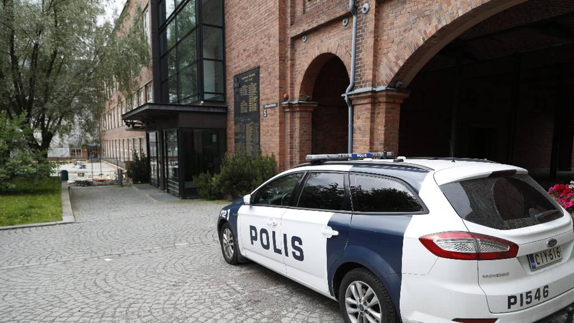 In this photo taken on Tuesday, July 5, 2016, a police car is parked outside Pirkanmaa district court in Tampere Finland. A Finnish prosecutor has charged six members of the Cuban national volleyball team with aggravated rape. Prosecutor Leena Koivuniemi says all six have denied the charges. She declined Tuesday, Aug. 16 to give further details pending the court case. Eight Cuban players were originally arrested following allegations that a woman was raped at a hotel where the team was staying in the city of Tampere. Two were later released. (Kalle Parkkinen/Lehtikuva via AP)