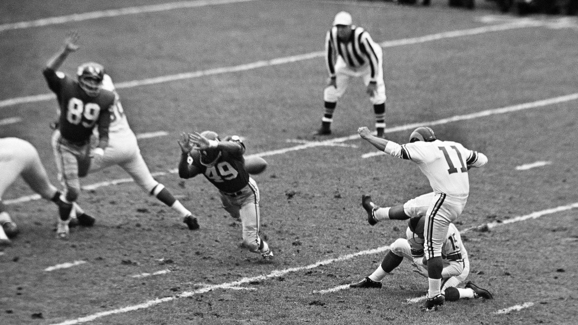 In this Oct. 22, 1961, file photo, New York Giants halfback Erich Barnes (49) blocks field goal-attempt by Los Angeles Rams' Danny Villanueva (11) in the first period of NFL game in New York's Yankee Stadium. Villanueva, who was one of the NFL's first Latino kickers and a pioneer of Spanish-language television, has died. He was 77. (AP Photo, File)