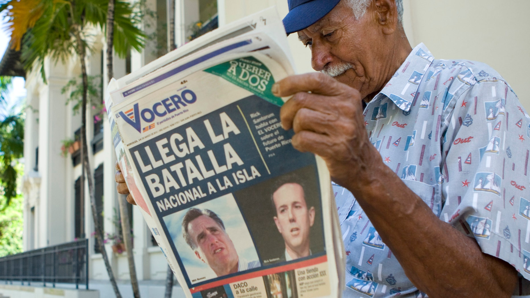 """SAN JUAN, PUERTO RICO - MARCH 14:  Carlos Diaz, 84, reads local newspaper El Vocero with a front page depicting both Mitt Romney and Rick Santorum and a headline reading, """"The National Battle Arrives on the Island.  (Photo by Christopher Gregory/Getty Images)"""