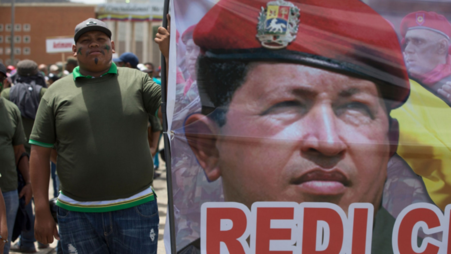 A supporters of Venezuela's President Nicolas Maduro stands next to a picture of Venezuela's late President Hugo Chavez prior a civilian and military exercise at fort Tiuna in Caracas, Venezuela, Saturday, March 14, 2015. President Maduro is expected to oversee military exercises across the country, which are intended to show the South American countryâs strength in the face of U.S. threats. (AP Photo/Fernando Llano)