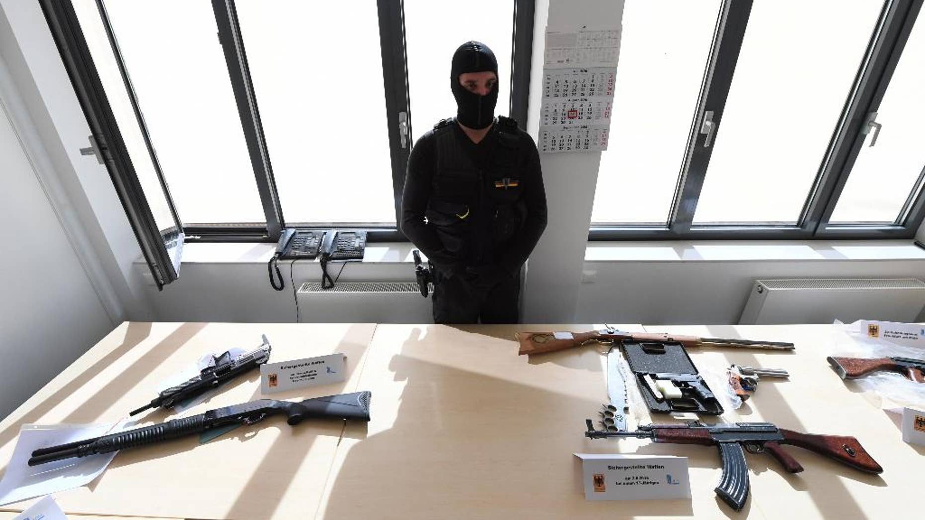 The Customs Office in Frankfurt displays  seized  firearms  at a press conference in Frankfurt, Germany, Wednesday Aug. 17, 2016.  German prosecutors say the teenager who went on a shooting rampage at a Munich mall last month, killing nine people and then himself, paid 4,350 euros (nearly $4,900) for his gun and ammunition. Authorities on Tuesday arrested a 31-year-old unemployed salesman accused of selling the Glock 17 pistol to the 18-year-old gunman. That connection surfaced as the suspected dealer was being investigated for other sales. (Arne Dedert/dpa via AP)