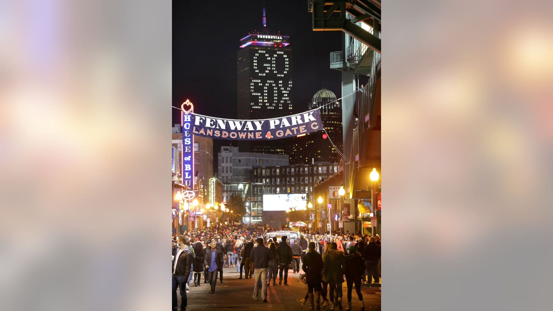 "The words ""Go Sox"" are illuminated on a side of the Prudential Tower, top, as people walk along a street outside Fenway Park during Game 6 of baseball's World Series between the Boston Red Sox and St. Louis Cardinals, Wednesday, Oct. 30, 2013, in Boston. (AP Photo/Steven Senne)"