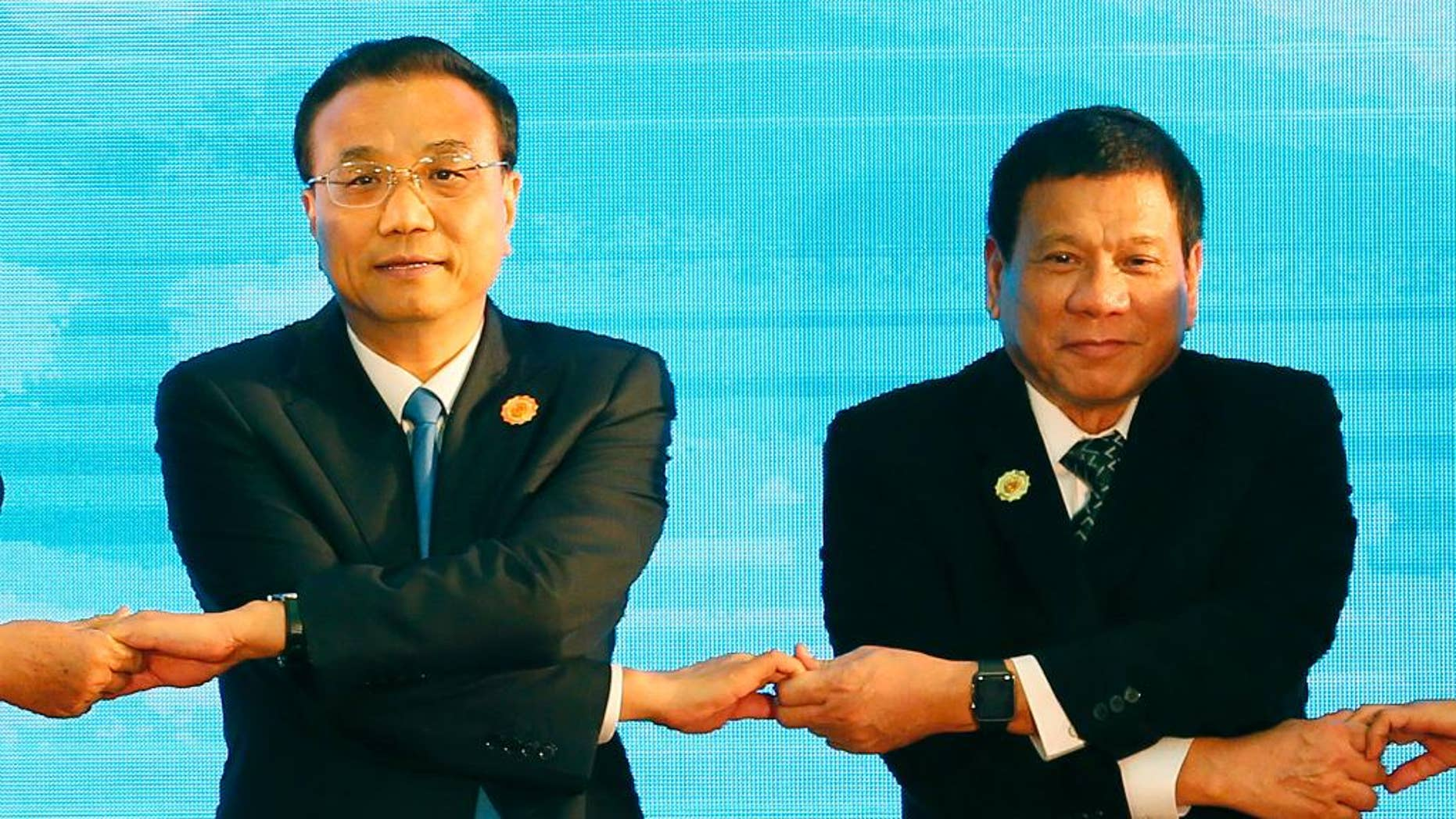 FILE - In this Sept. 7, 2016 file photo, Chinese Prime Minister Li Keqiang, left, and Philippine President Rodrigo Duterte link arms during the ASEAN Plus Three summit in the ongoing 28th and 29th ASEAN Summits and other related summits at the National Convention Center in Vientiane, Laos. After lashing out at longtime ally America, the new Philippine president is making a state visit to China in a charm offensive that will help define how far he wants to shift allegiance from treaty ally the U.S. to an Asian superpower locked in a territorial standoff with his small, impoverished country. (AP Photo/Bullit Marquez, File)