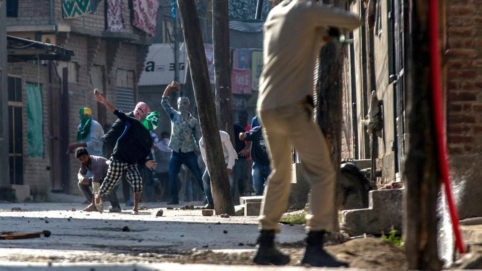 Kashmiri protesters throw stones and bricks at an Indian policeman as he prepares to fire pallet gun during a protest in Srinagar, Indian controlled Kashmir, Friday, Oct. 7, 2016. Authorities imposed a curfew in many parts of the Indian-controlled Kashmir to prevent a protest march to the disputed Himalayan region's office of United Nations Military Observer Group in India and Pakistan (UNMOGIP) called by separatist leaders seeking end of Indian rule. (AP Photo/Dar Yasin)