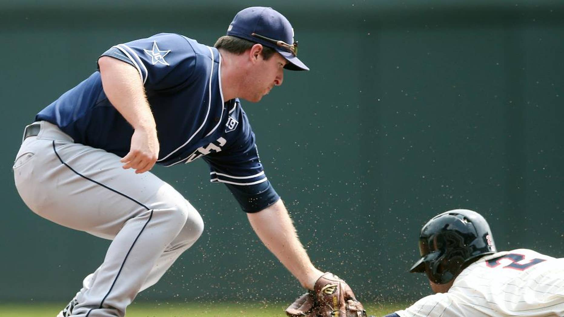 San Diego Padres second baseman Jedd Gyorko, left, reaches to tag Minnesota Twins' Brian Dozier who was called safe as he stole second base in the first inning of a baseball game, Wednesday, Aug. 6, 2014, in Minneapolis. (AP Photo/Jim Mone)