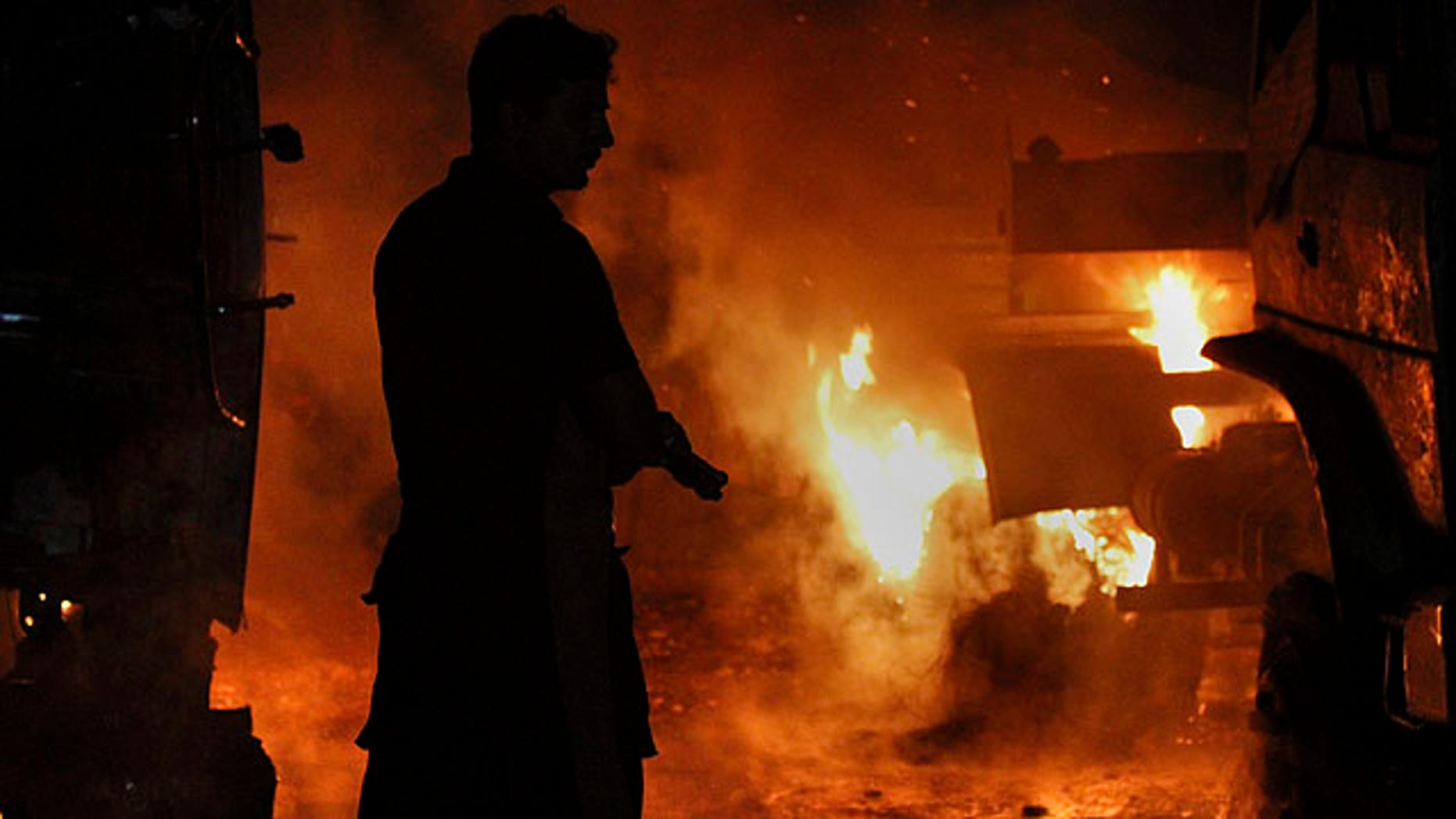 Oct. 4, 2010: A Pakistani fire fighter prepares to extinguish burning oil tankers after militants attacked a terminal in Rawalpindi, Pakistan.