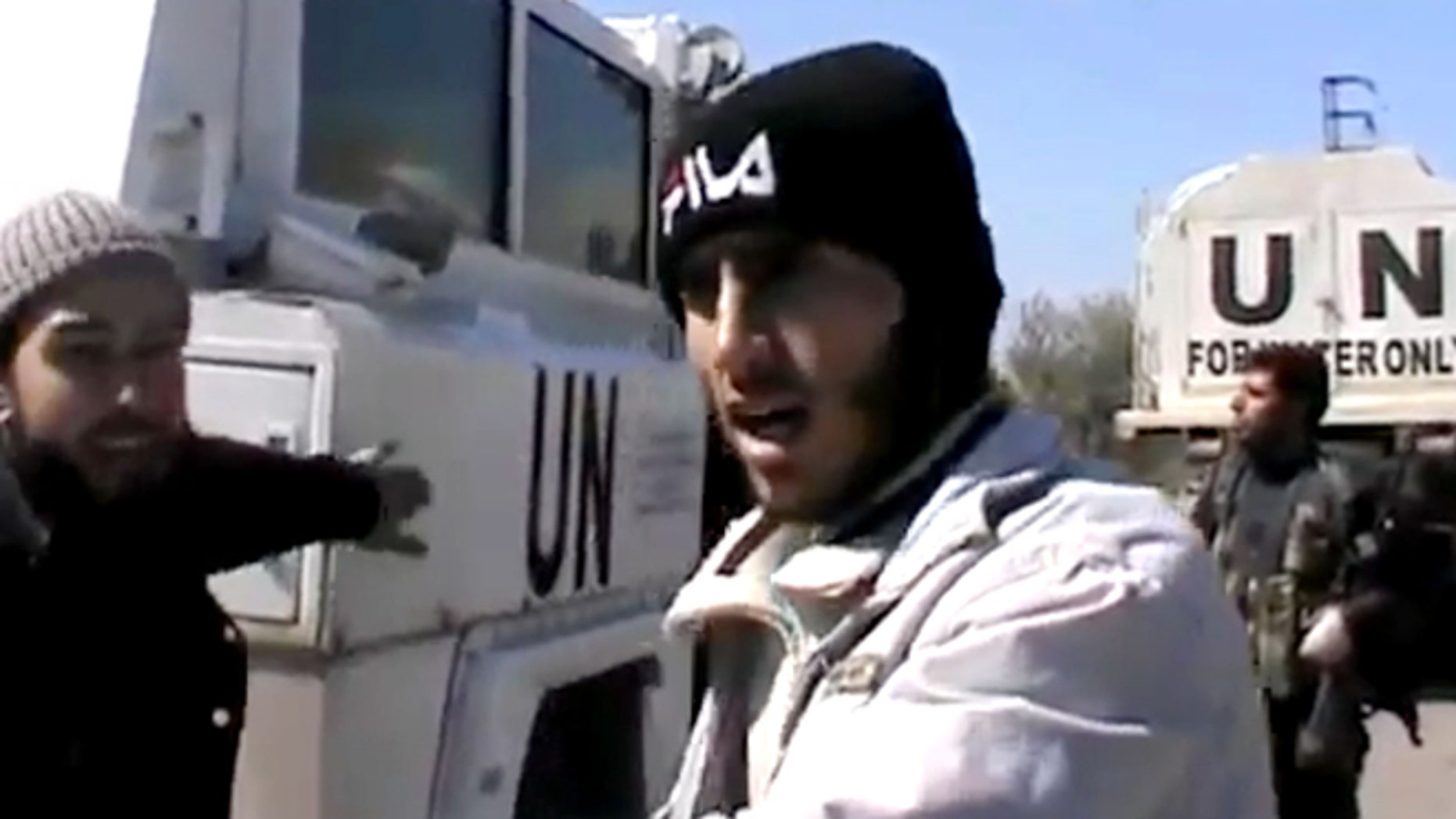 In this Wednesday, March 6, 2013 image taken from video obtained from the Ugarit News, which has been authenticated based on its contents and other AP reporting, Free Syrian Army fighters stand next to United Nations Disengagement Observer vehicles near Golan Heights in the southern province of Daraa, Syria.