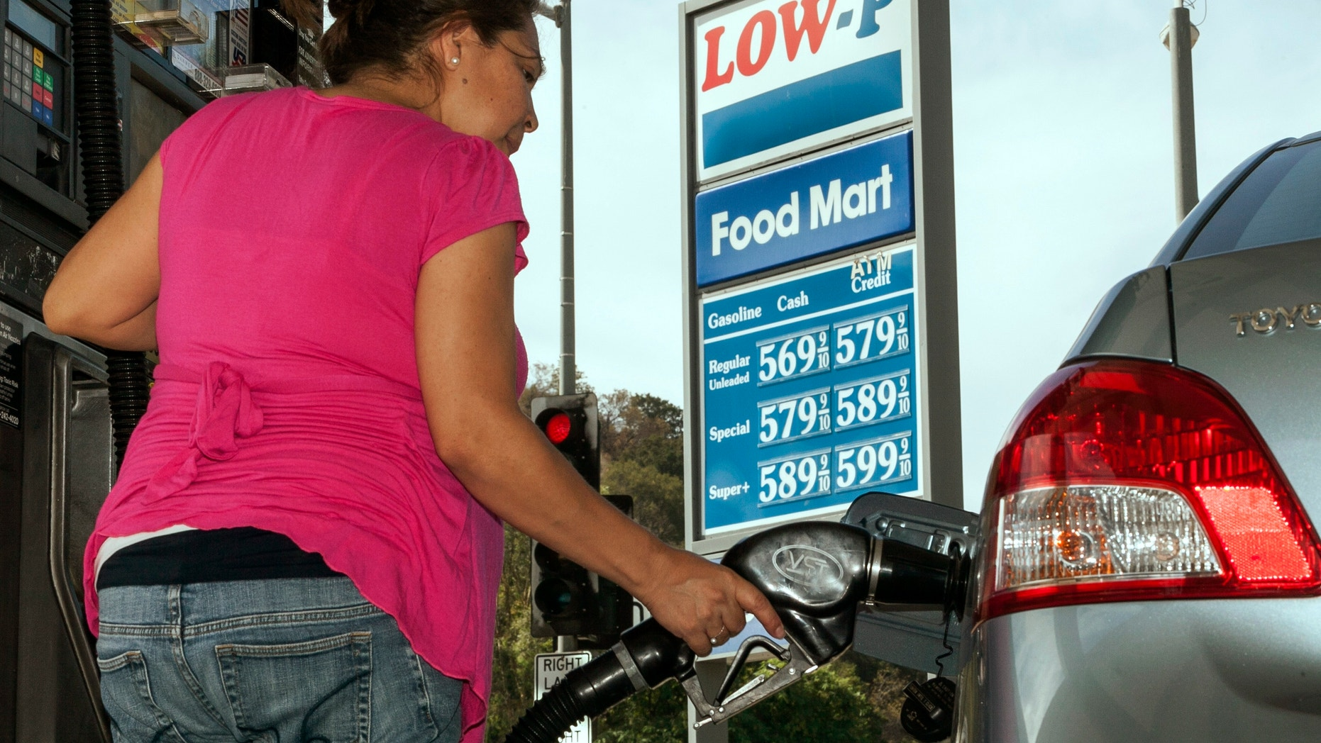 Oct. 5, 2012: Motorist Elisabeth Chavarria fills up only six dollars worth of gas to be able to drive home Friday, Oct. 5, 2012, at the Low-P, an independent gas station in Calabasas, Calif.