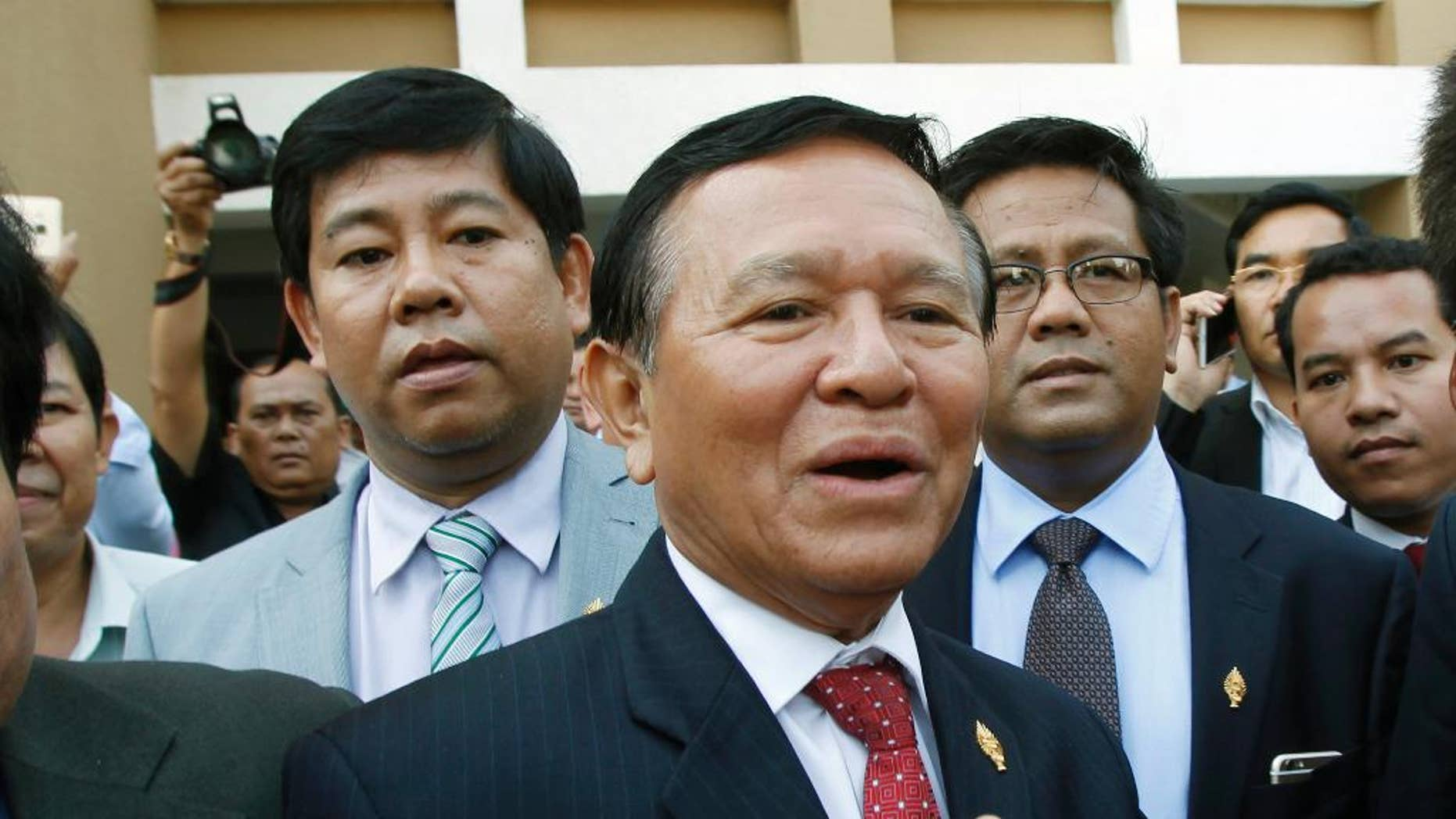 In this April 8, 2015 photo, Cambodia's main opposition Cambodia National Rescue Party Deputy President and National Assembly Deputy President Kem Sokha, center, speaks to the media outside the Phnom Penh Municipality Court in Phnom Penh, Cambodia. The senior leader of Cambodia's opposition party was stripped of his post as the vice-president of parliament in a skewed and unexpected vote Friday, Oct. 30, 2015 that was attended only by the ruling party. (AP Photo/Heng Sinith)