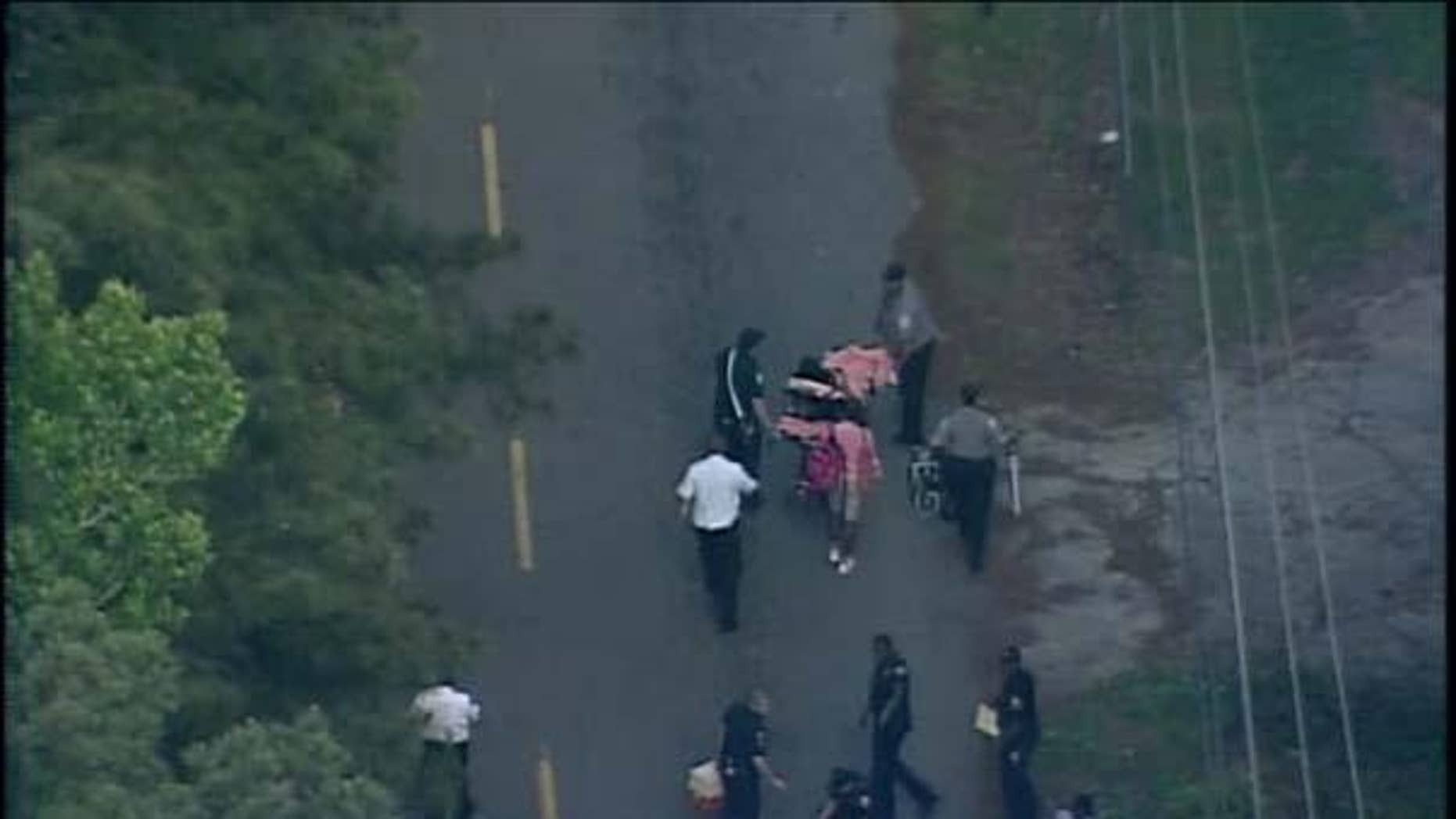 May 13, 2014: Emergency personnel take away a shooting victim on a stretcher outside Therrell High School. (MyFoxAtlanta.com)