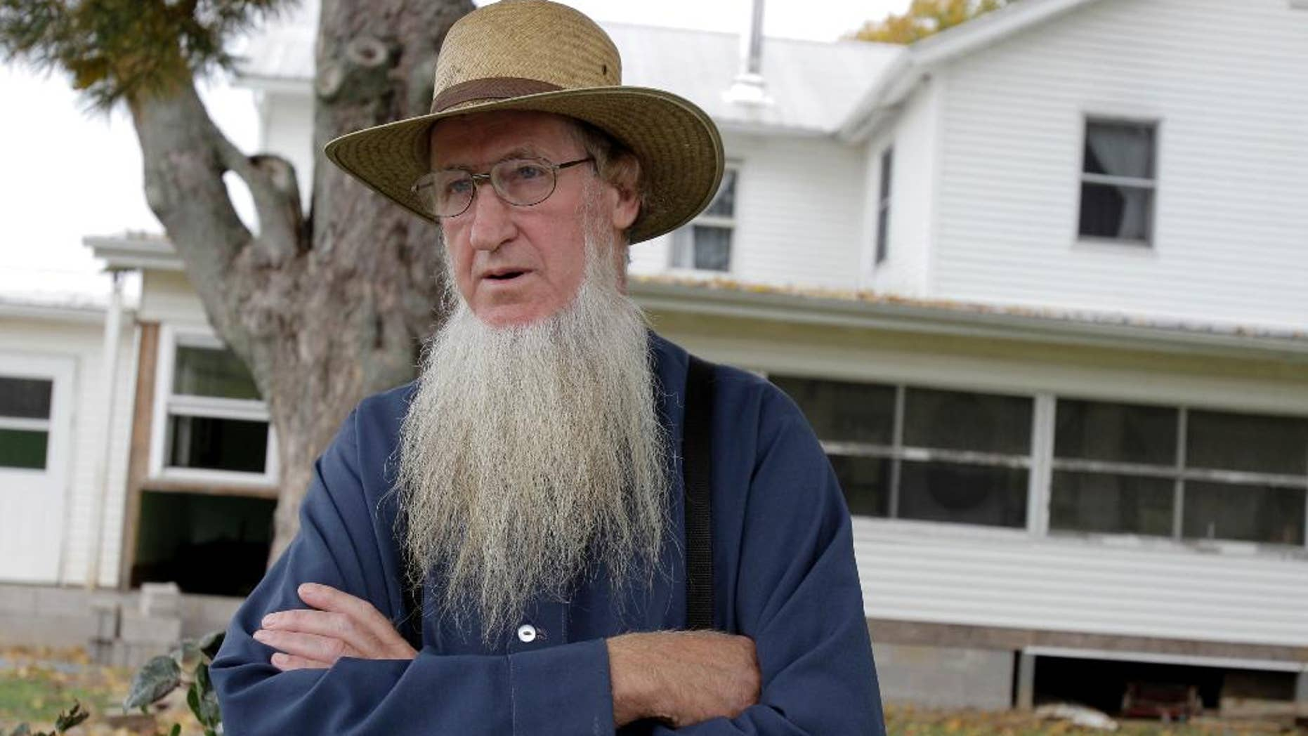 FILE - In this Oct. 10, 2011 file photo, Sam Mullet stands in front of his home in Bergholz, Ohio. Mullet, the leader of a breakaway Amish group in Ohio whose hate crime convictions for beard- and hair-cutting attacks were overturned, wants a federal judge to release him from prison when he's resentenced next month. All 16 members found guilty in the attacks that targeted Amish who had criticized them are to be resentenced March 2 in Cleveland since the 6th U.S. Circuit Court of Appeals overturned the most serious convictions against them. Defense attorneys for Mullet said his 15-year sentence should be reduced to the three years he's already served. (AP Photo/Amy Sancetta, File)