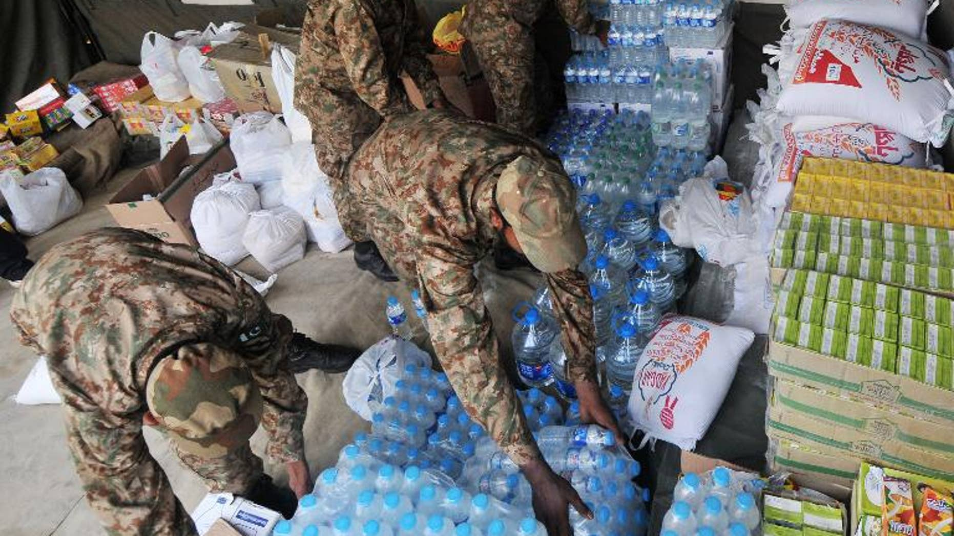 Pakistani army soldiers arrange relief supplies for earthquake survivors in Lahore on September 29, 2013.