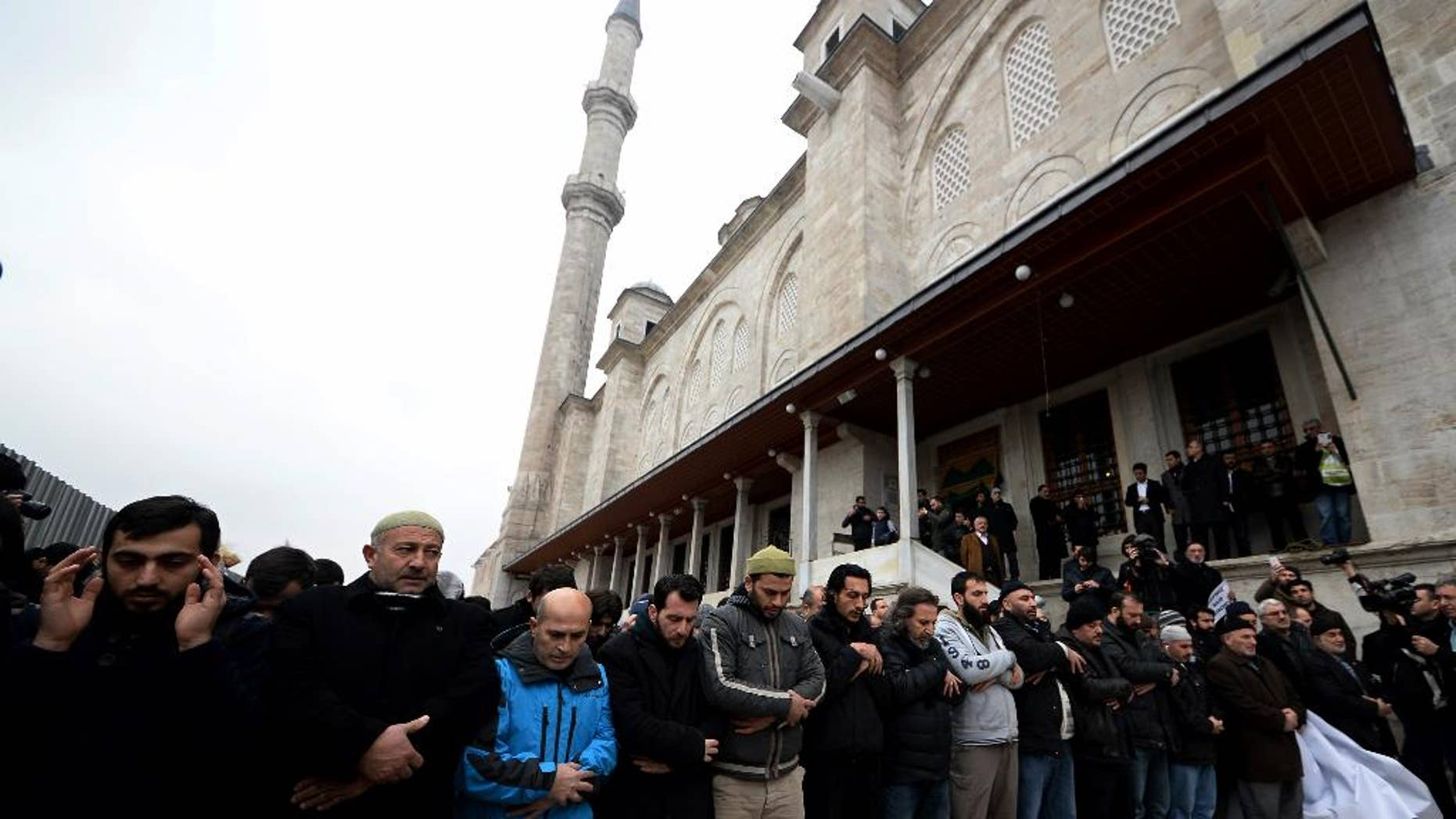 """Members of pro-Islamic groups shout slogans after they held funeral prayers on Friday to honor Cherif and Said Kouachi, the gun-toting brothers who killed 12 people last week in Paris, in Istanbul, Turkey, Friday, Jan. 16, 2015. Some 160 people — all of them men — shouted """"God is great!"""" and they held a banner showing former al-Qaida leader Osama Bin Laden's picture on one side, and the Kouachi brothers superimposed over the Parisian skyline on the other. Smaller posters with """"We are all Cherif"""" and """"We are all Said"""" were bounced up. (AP Photo)"""