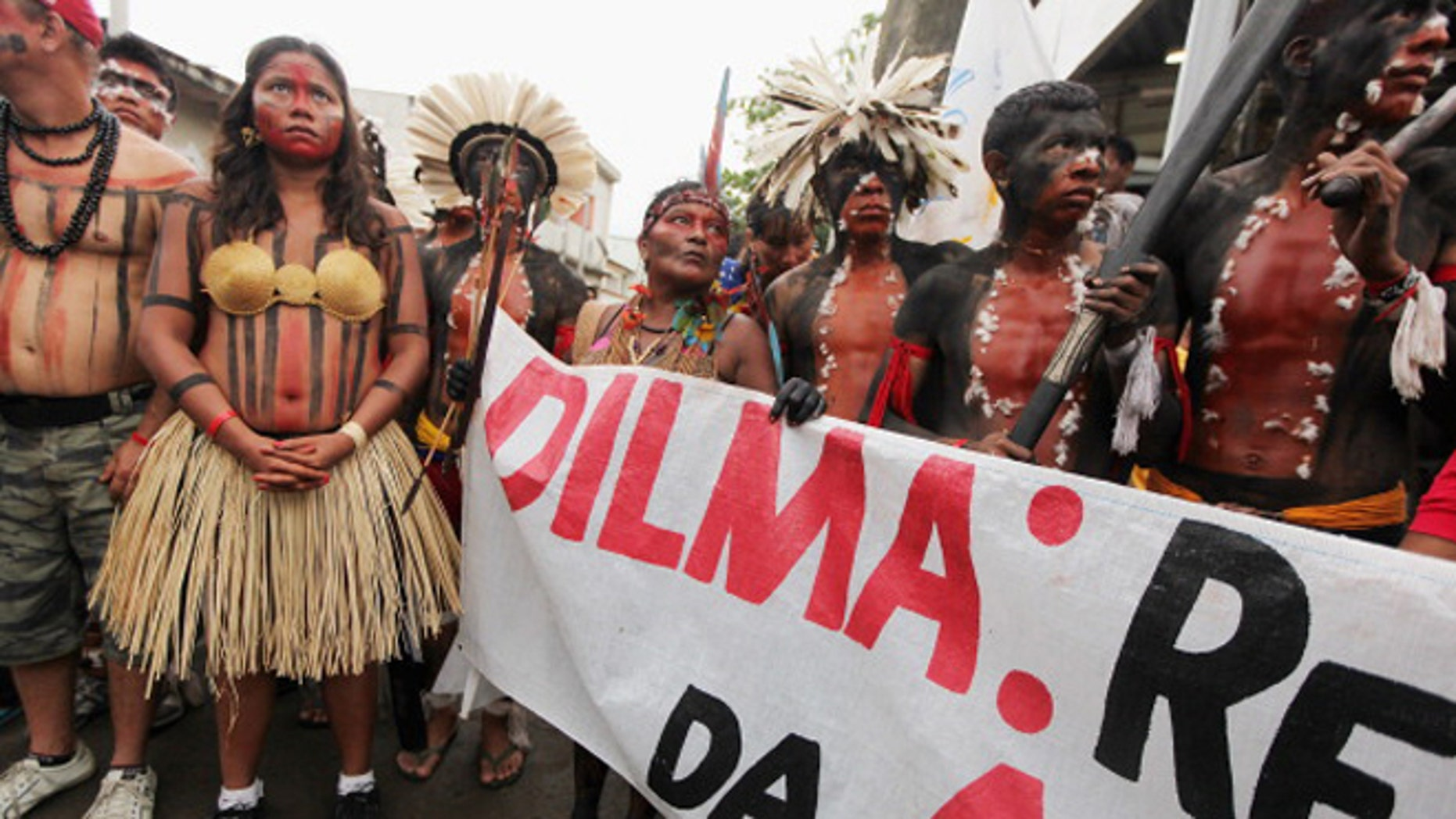 Indigenous and protesters look on during a march through the decades-old Vila Autodromo squatter settlement before demonstrating outside an entrance to the Rio + 20 conference on June 20, 2012 in Rio de Janeiro, (Photo by Mario Tama/Getty Images)