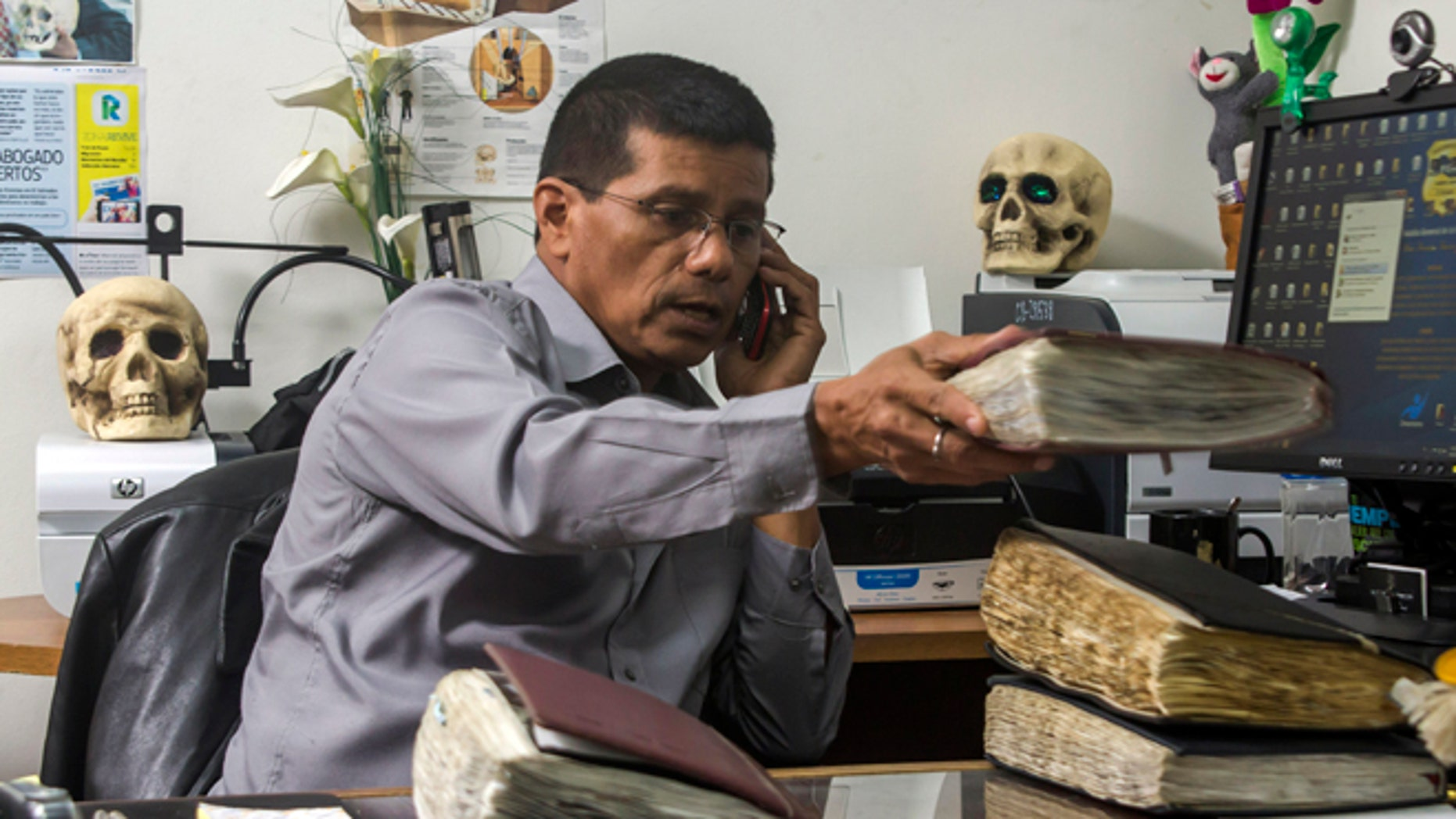 In this Oct. 6, 2014, photo, criminologist Israel Ticas talks on the phone as he stacks his field notebooks, at his office in San Salvador, El Salvador. Ticas got his start making drawings of the dead and models of crime scenes. He studied forensic science on his own and in 2002, convinced the attorney general to give him an office and authority for excavating clandestine cemeteries. (AP Photo/Salvador Melendez)