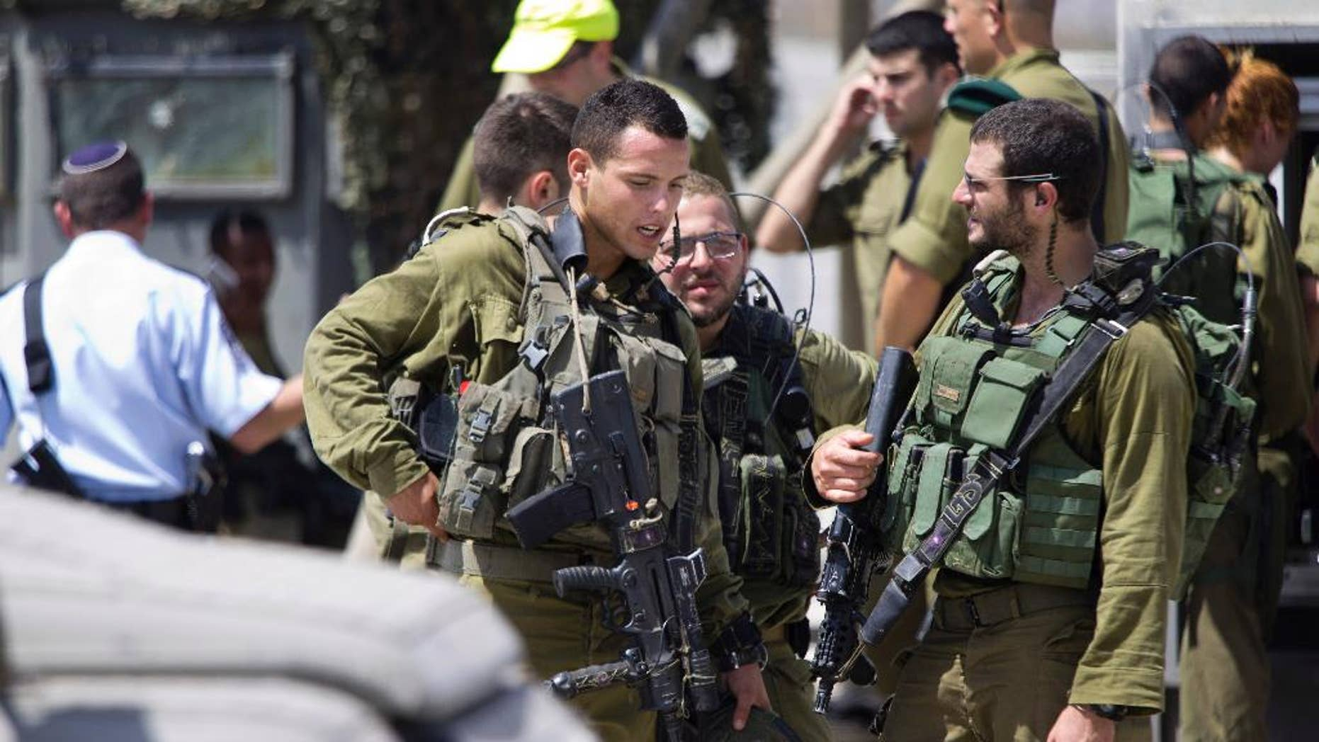Aug. 17, 2015: Israeli soldiers stand guard at a checkpoint near the West Bank of Nablus. Israel authorities say troops have shot and killed a Palestinian after he stabbed a guard at a West Bank checkpoint. Police spokeswoman Luba Samri says the man approached border police officers manning a checkpoint on Monday and told them he felt unwell.