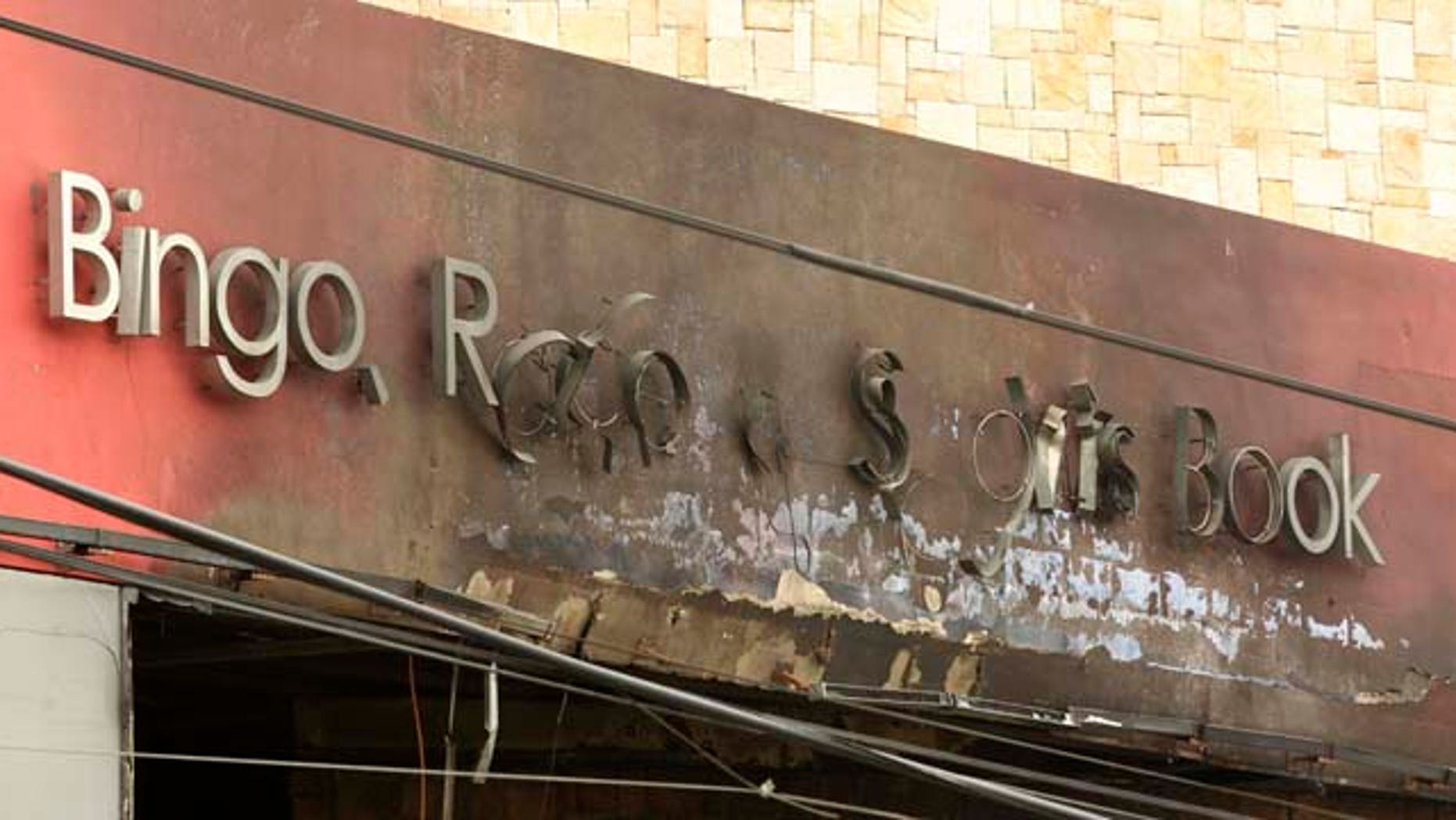 "The Casino Royale sign that once read ""Bingo, Race & Sports Book"" is charred from the deadly arson assault in Monterrey, Mexico, Friday Aug. 26, 2011. Mexican officials say a group of at least eight assailants poured gasoline inside the casino on Thursday, trapping dozens of people inside and killing at least 52 people. Mexico's President Felipe Calderon declared three days of mourning Friday for the 52 victims of the casino fire set by presumed drug traffickers, branding the attackers ""true terrorists"" and ordering authorities to offer a $2.4 million reward for their capture. (AP Photo/Hans-Maximo Musielik)"