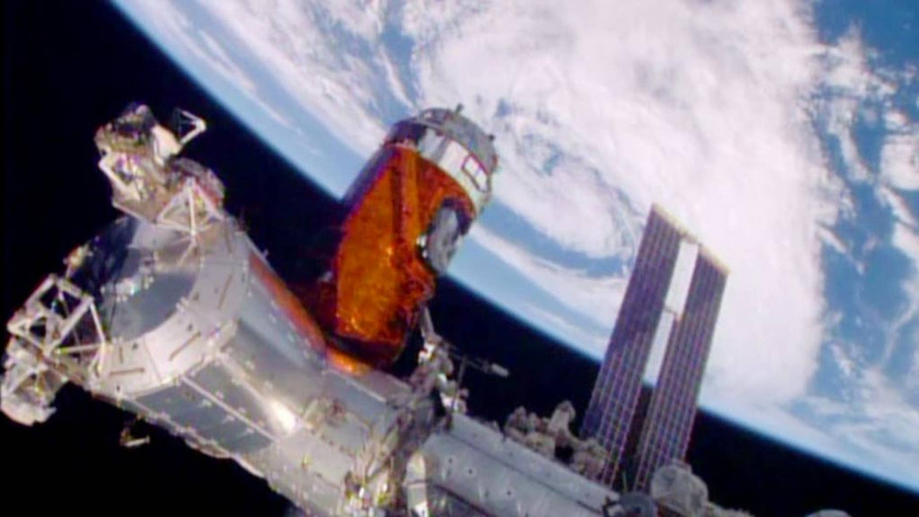 In a photo provided by NASA, a cargo ship from a Japanese company is bolted into place on the International Space Station Monday, Aug. 24, 2015. A Japanese company known for its whiskey and other alcoholic beverages included five types of distilled spirits in the cargo ship that arrived at the space station Monday. The samples will spend at least a year in orbit to see if alcoholic beverages mellow the same in space as they do on Earth. The station's big robotic arm, operated by Japanese astronaut Kimiya Yui, grabbed onto the supply craft launched Wednesday by his homeland. Flight controllers helped anchor it down. NASA also has considerable equipment aboard the supply capsule. (NASA via AP)