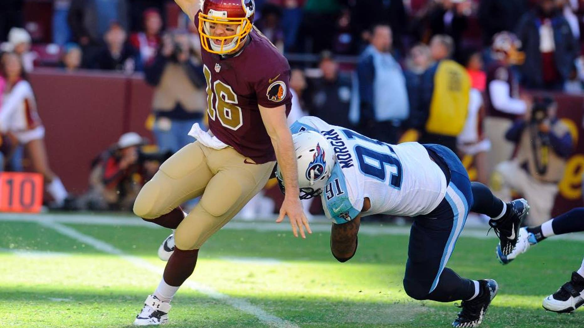 Washington Redskins quarterback Colt McCoy (16) avoids Tennessee Titans outside linebacker Derrick Morgan (91) during the second half of an NFL football game, Sunday, Oct. 19, 2014, in Landover, Md. The Redskins won 19-17. (AP Photo/Richard Lipski)