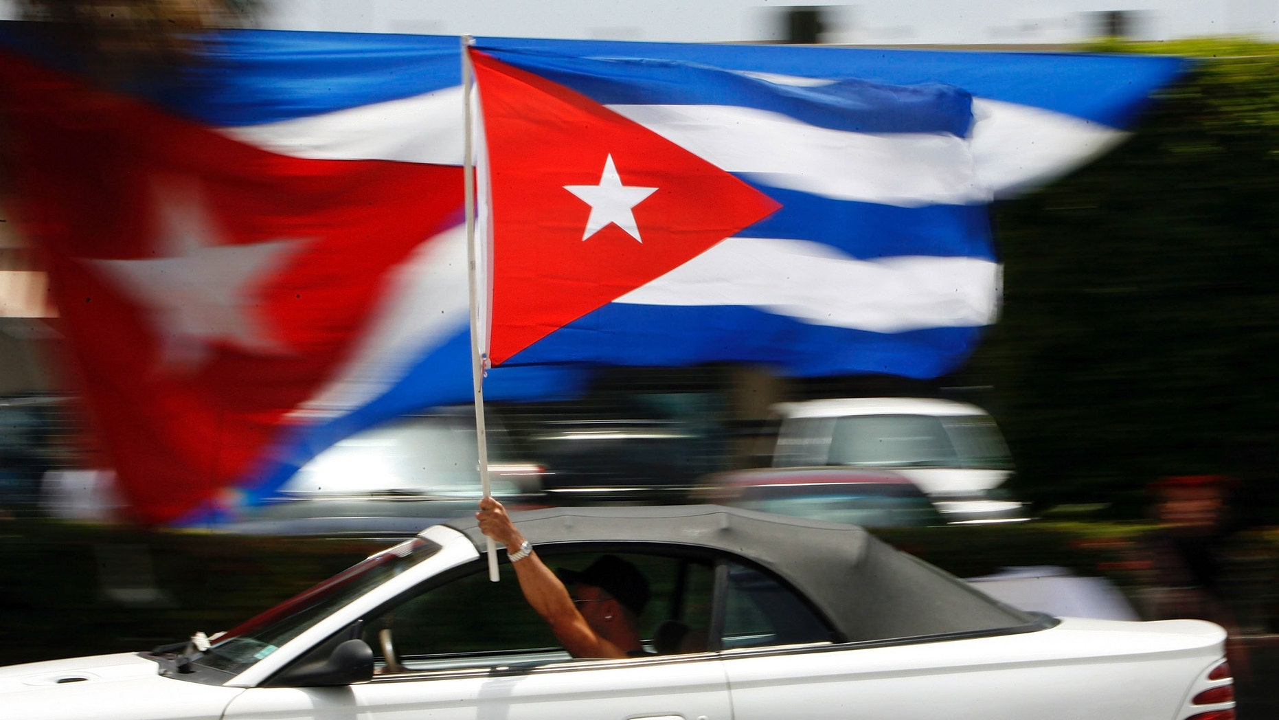 MIAMI - AUGUST 1:  A motorist waves a Cuban flag while cruising down the famous Calle Ocho in the Little Havana neighborhood August 1, 2006 in Miami, Florida. Cuban Americans were celebrating the news that Fidel Castro had turned over power to his younger brother, Raul Castro, while he undergoes medical treatment for intestinal bleeding.  (Photo by Chip Somodevilla/Getty Images)