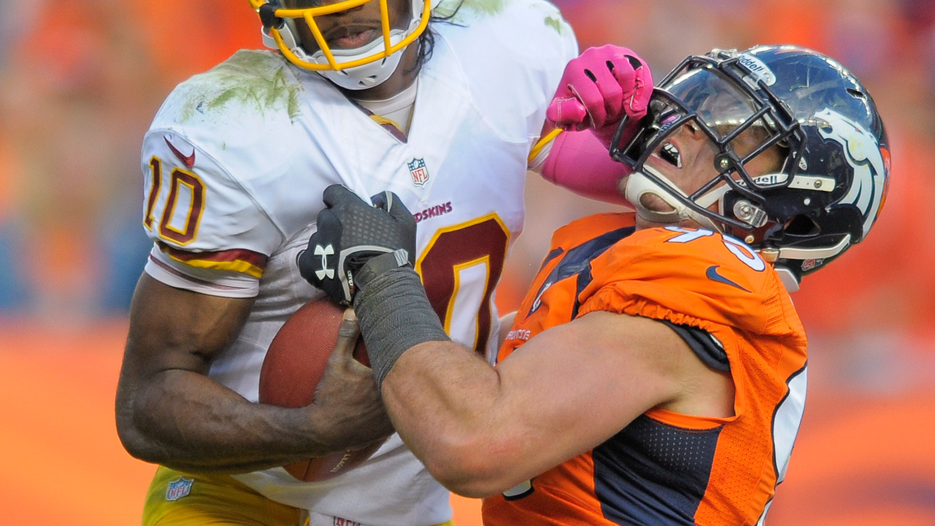 Washington Redskins quarterback Robert Griffin III (10) stiff arms Denver Broncos defensive end Derek Wolfe (95) in the fourth quarter of an NFL football game, Sunday, Oct. 27, 2013, in Denver. (AP Photo/Jack Dempsey)
