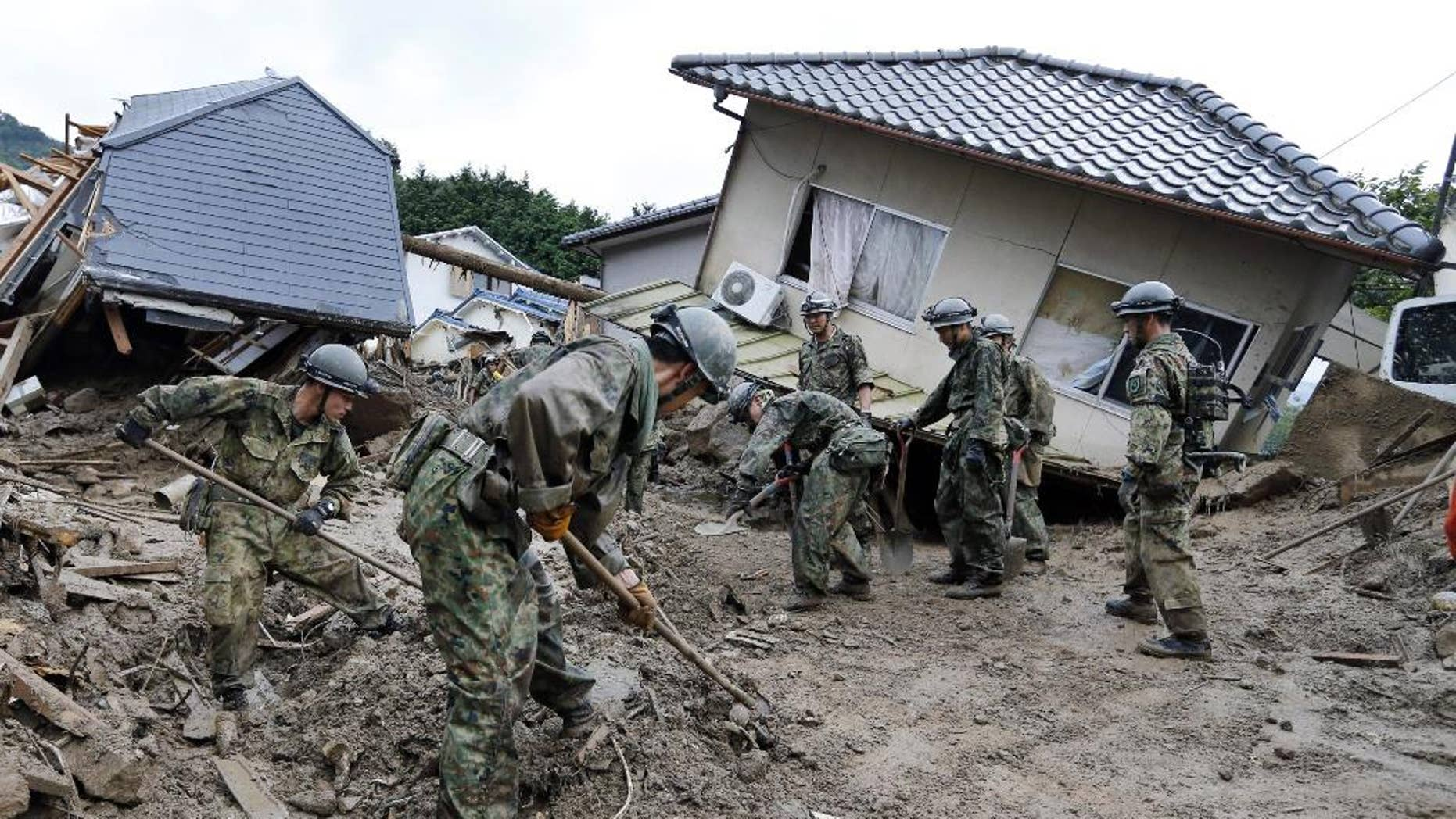 Aug. 21, 2014: Japan Ground Self Defense Force personnel search for missing residents in a mud-ridden residential area following a massive landslide in Hiroshima, western Japan. (AP/Kyodo News)