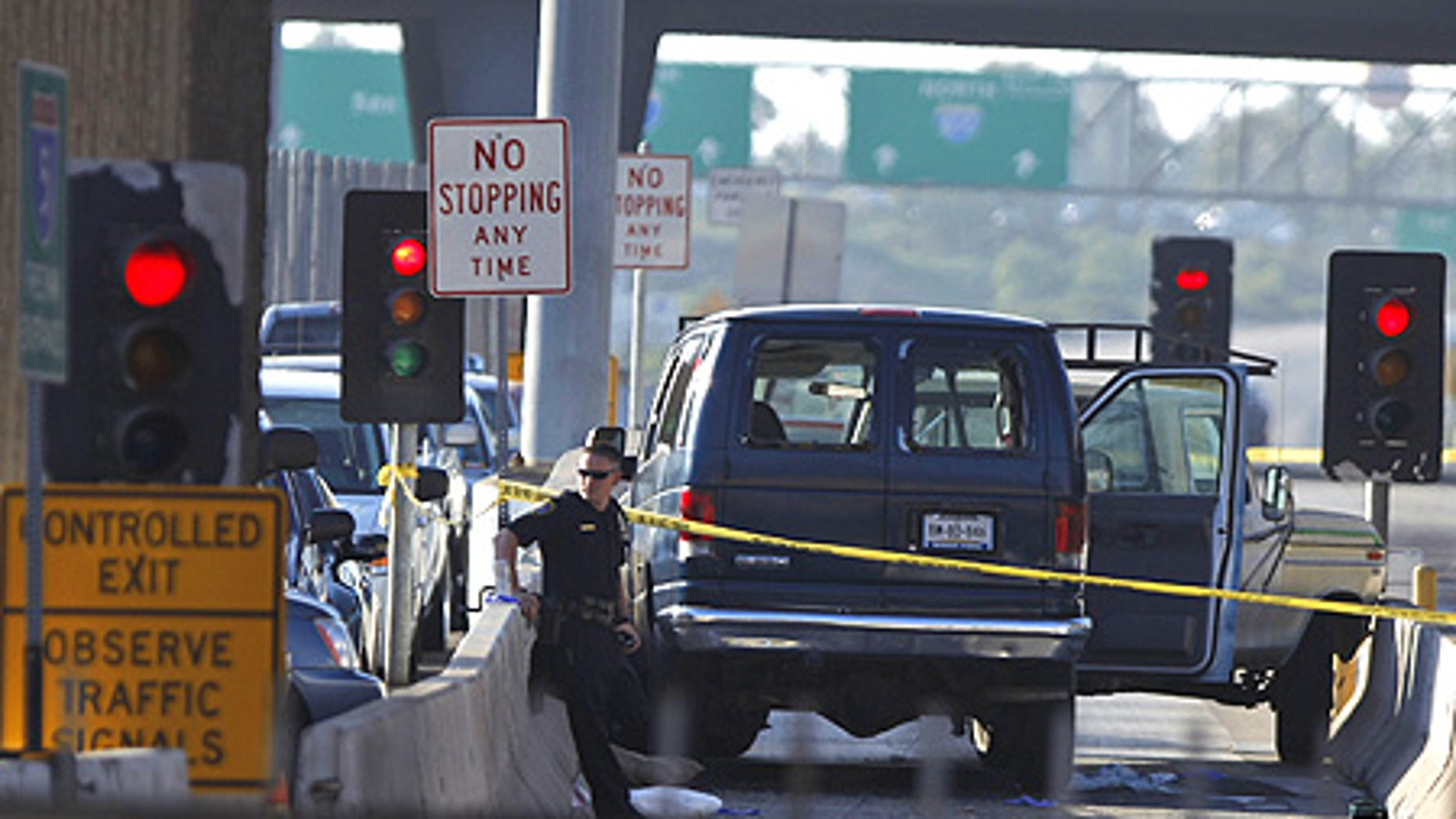 Sept. 22: A U.S. border officer is seen from Mexico's side of the San Ysidro port of entry guarding vehicles involved in a shooting.