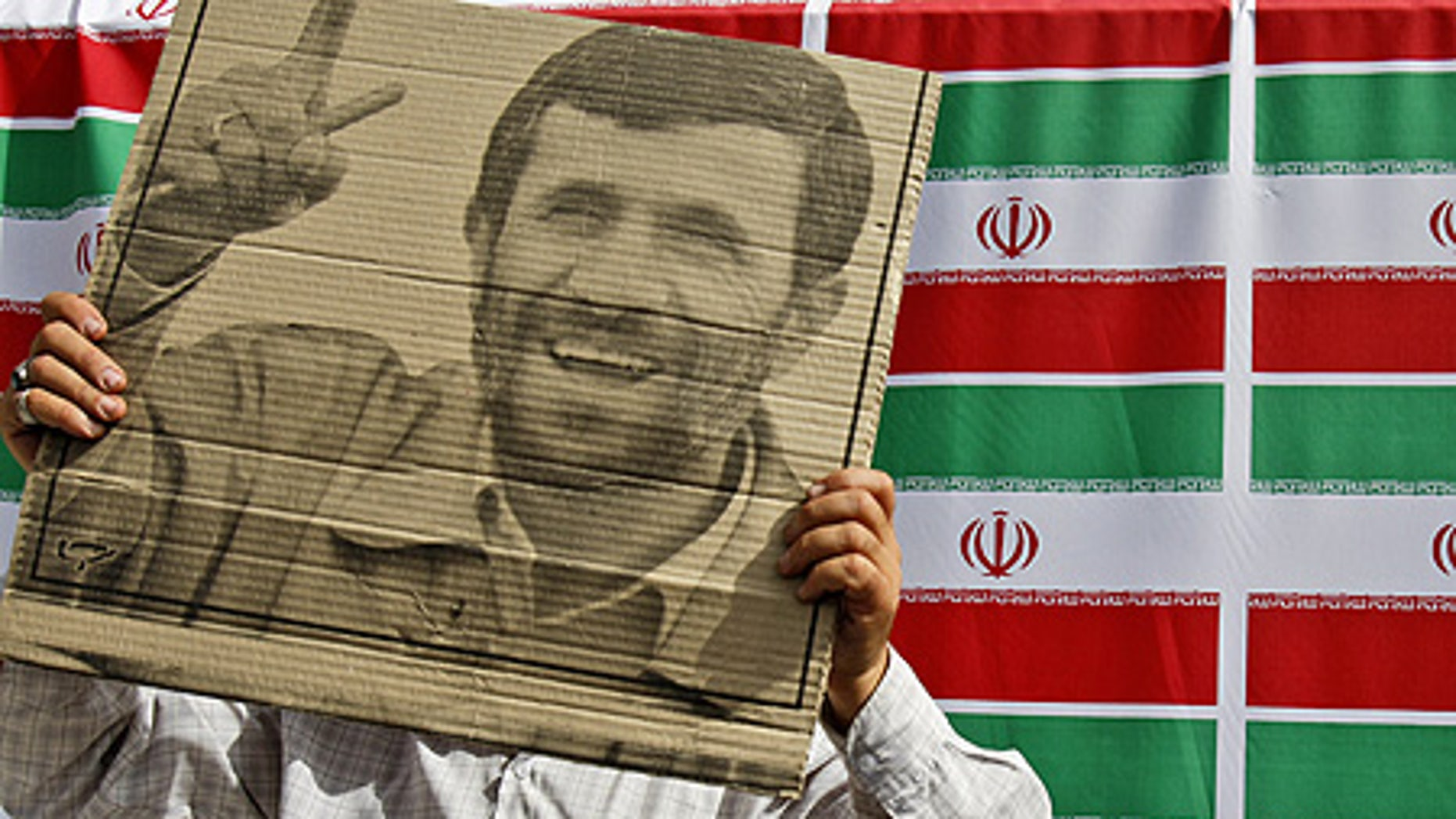June 10: A supporter of Mahmoud Ahmadinejad holds the president's poster during a rally in west Tehran.